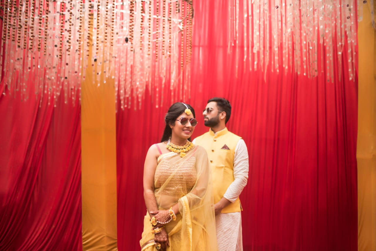couple in yellow in front of red background