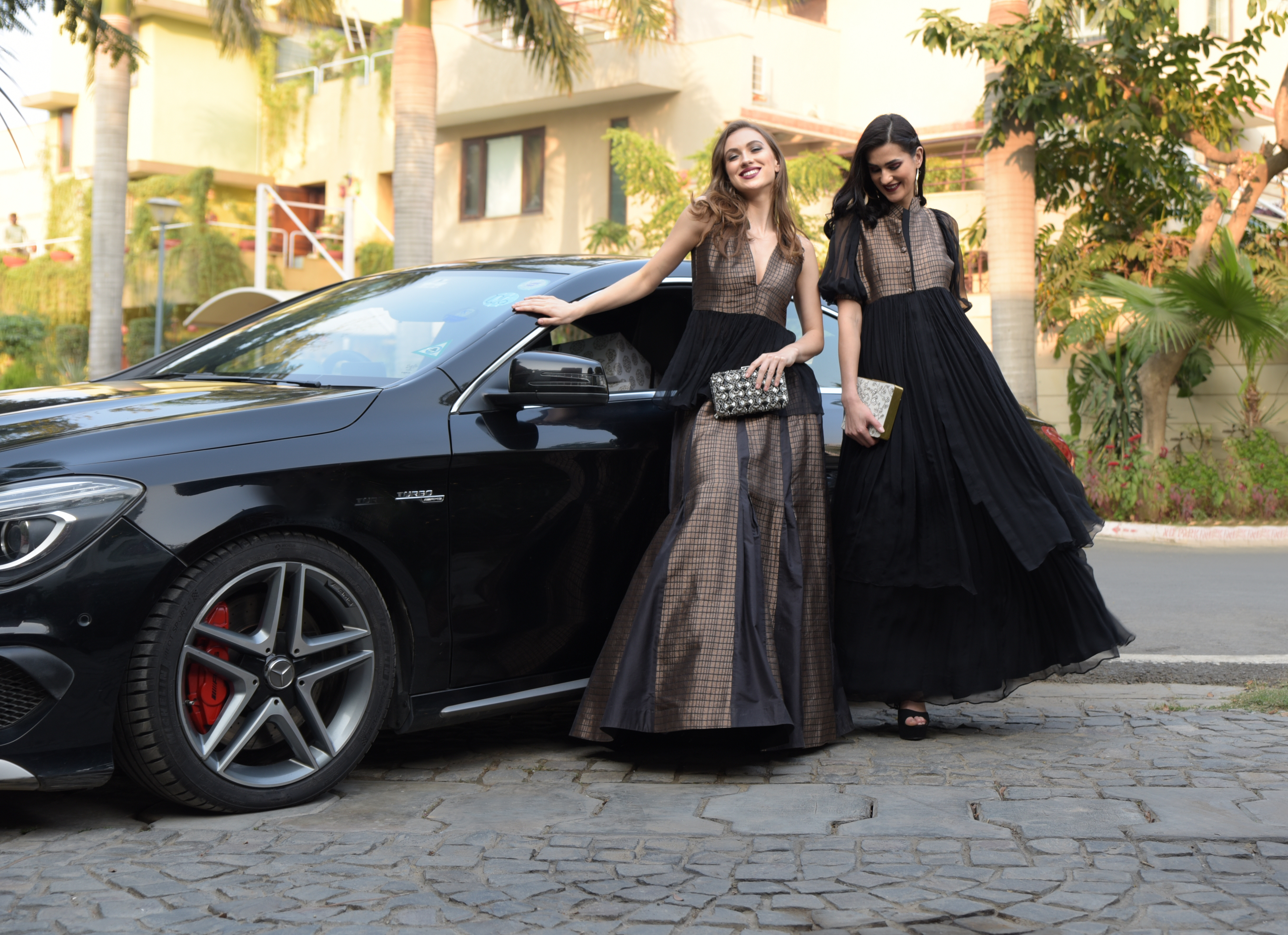 girls in black outfits pose in front of a black car