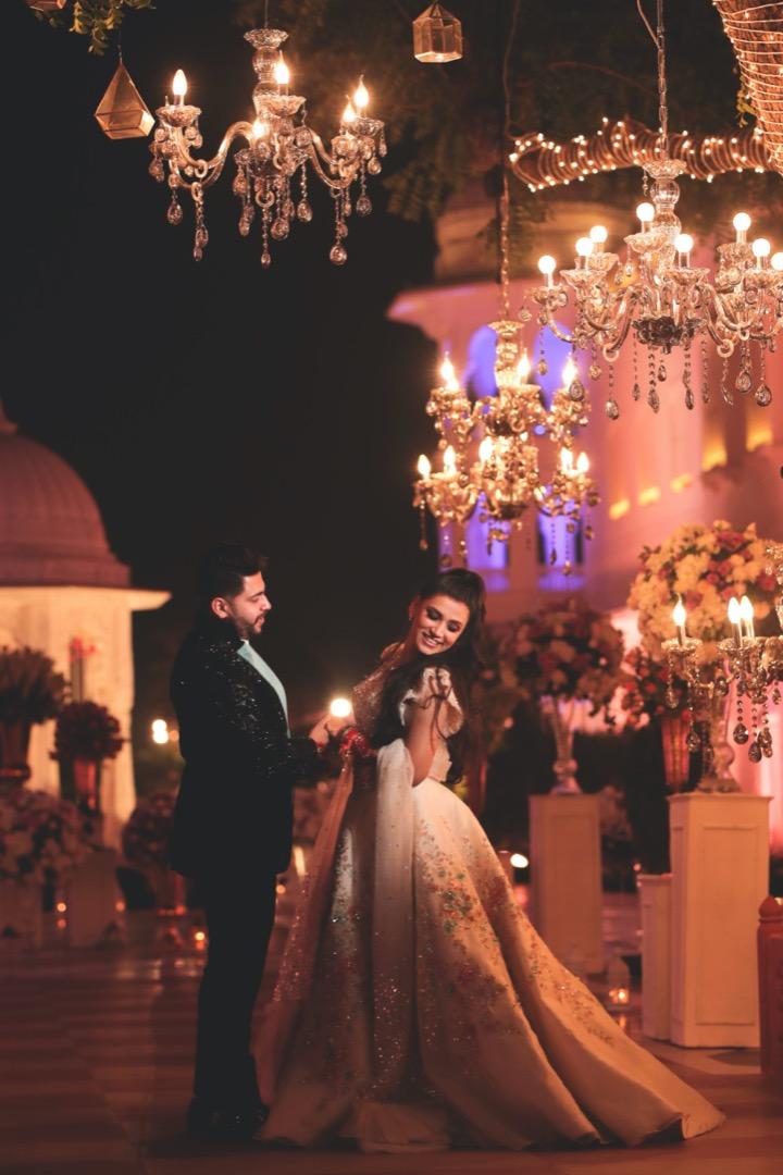 Dancing Bride & Groom Under Royal Reception Decor with Chandeliers