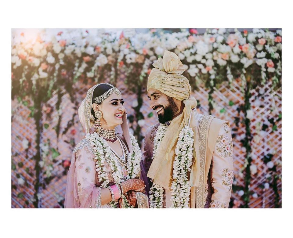 Happy Bride & Groom in Pastel Pink Outfits Amidst Dreamy Floral Decor Post Marriage Picture