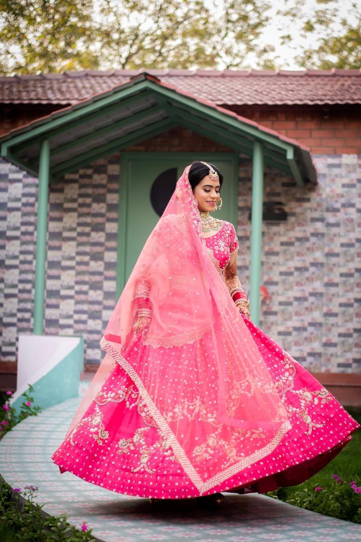bride twirl in her pink lehenga