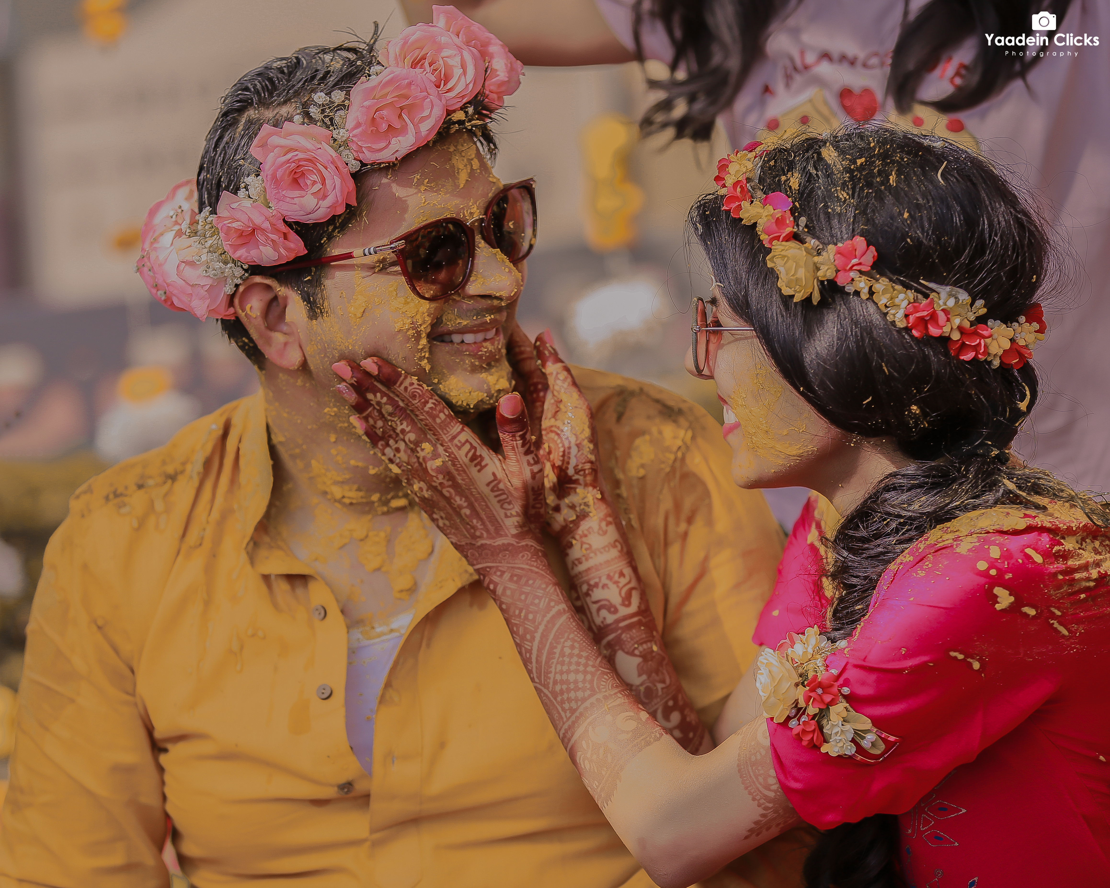 bride enjoying on her haldi in pink outfit and floral tiara