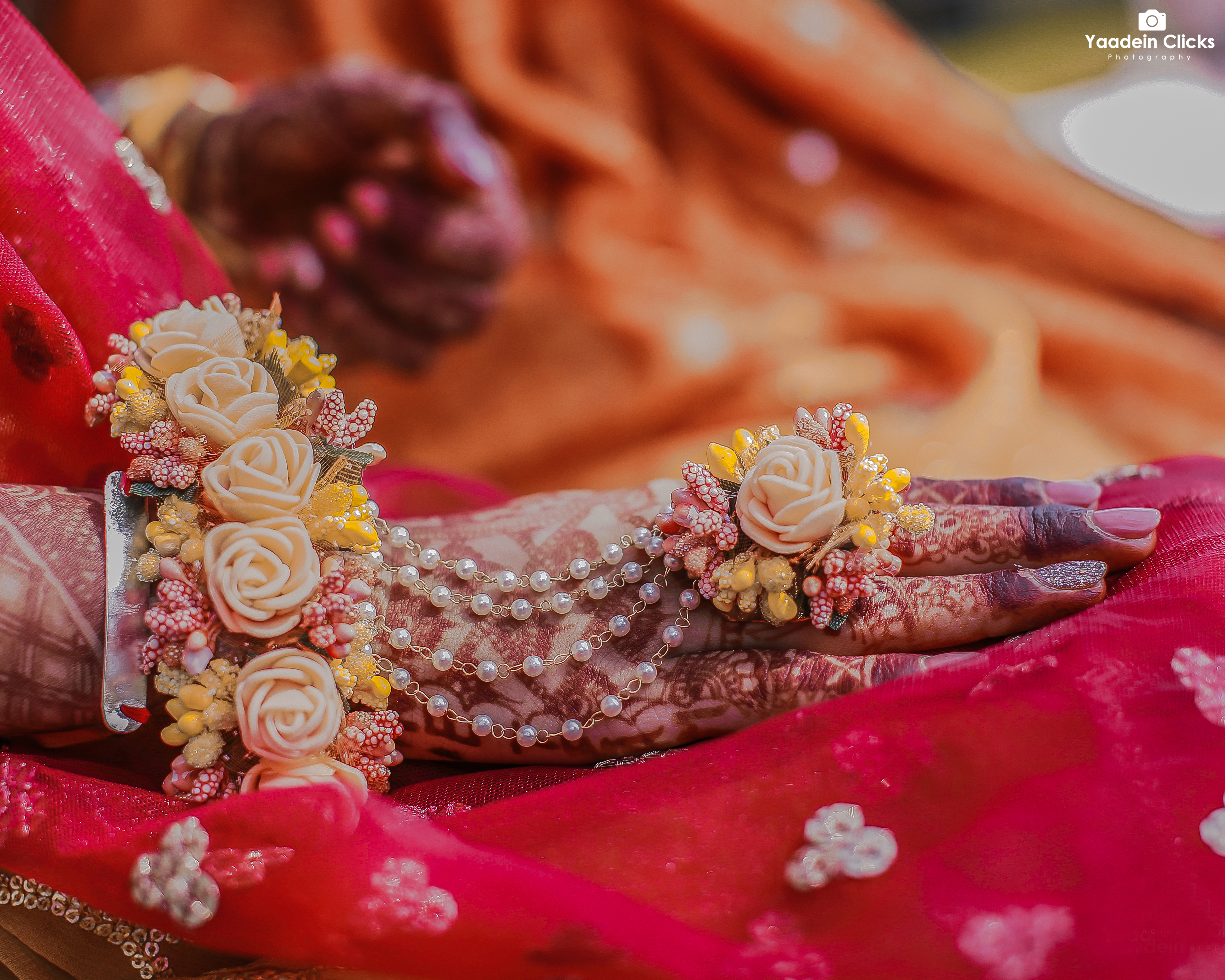Henna adorned hands with floral jewelry