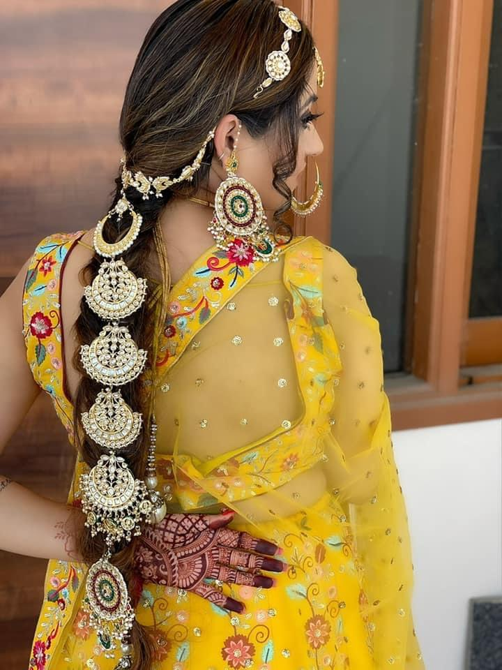 bride in yellow flaunting her heavy gold hair accessory