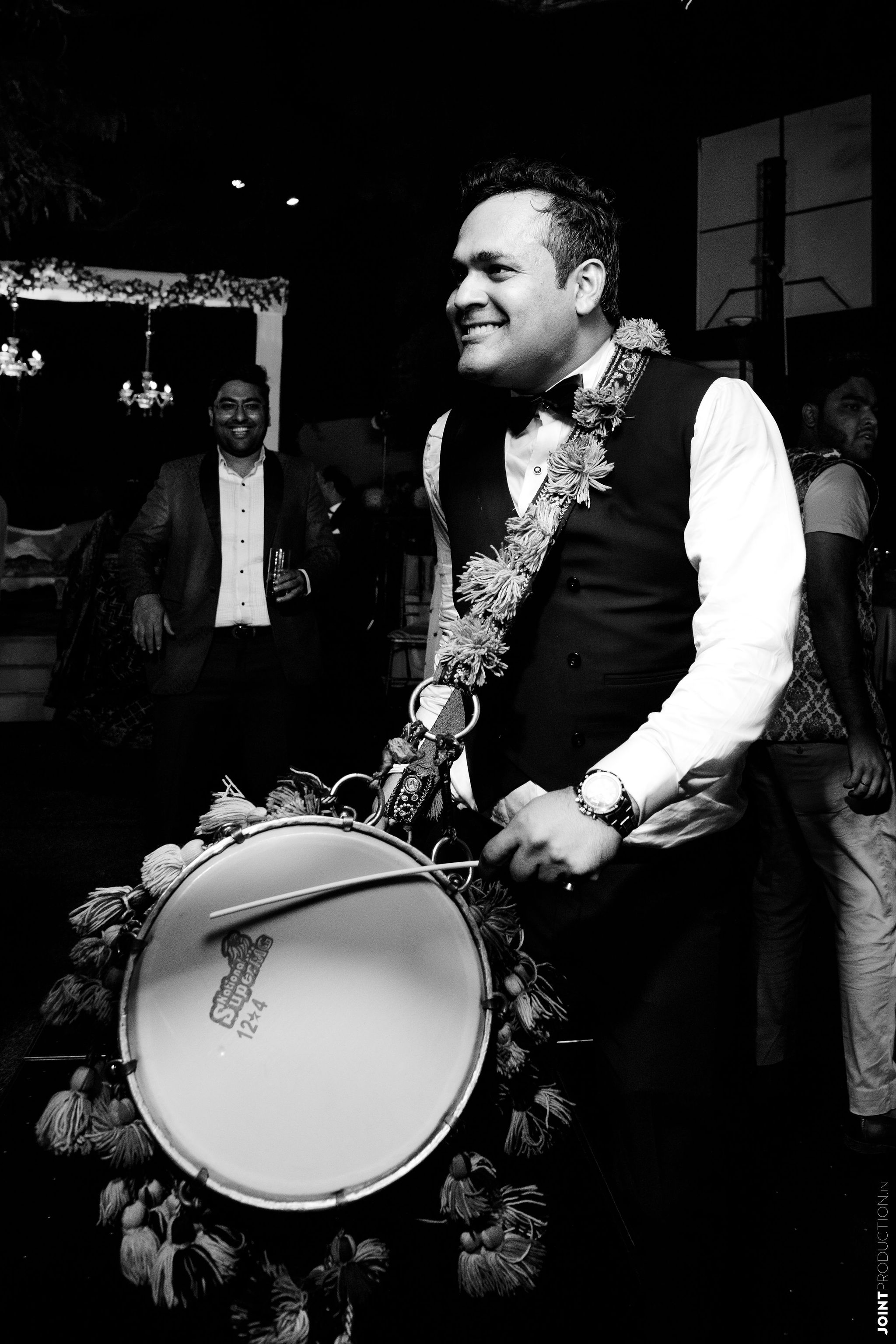 bnw shot of the groom playing dhol
