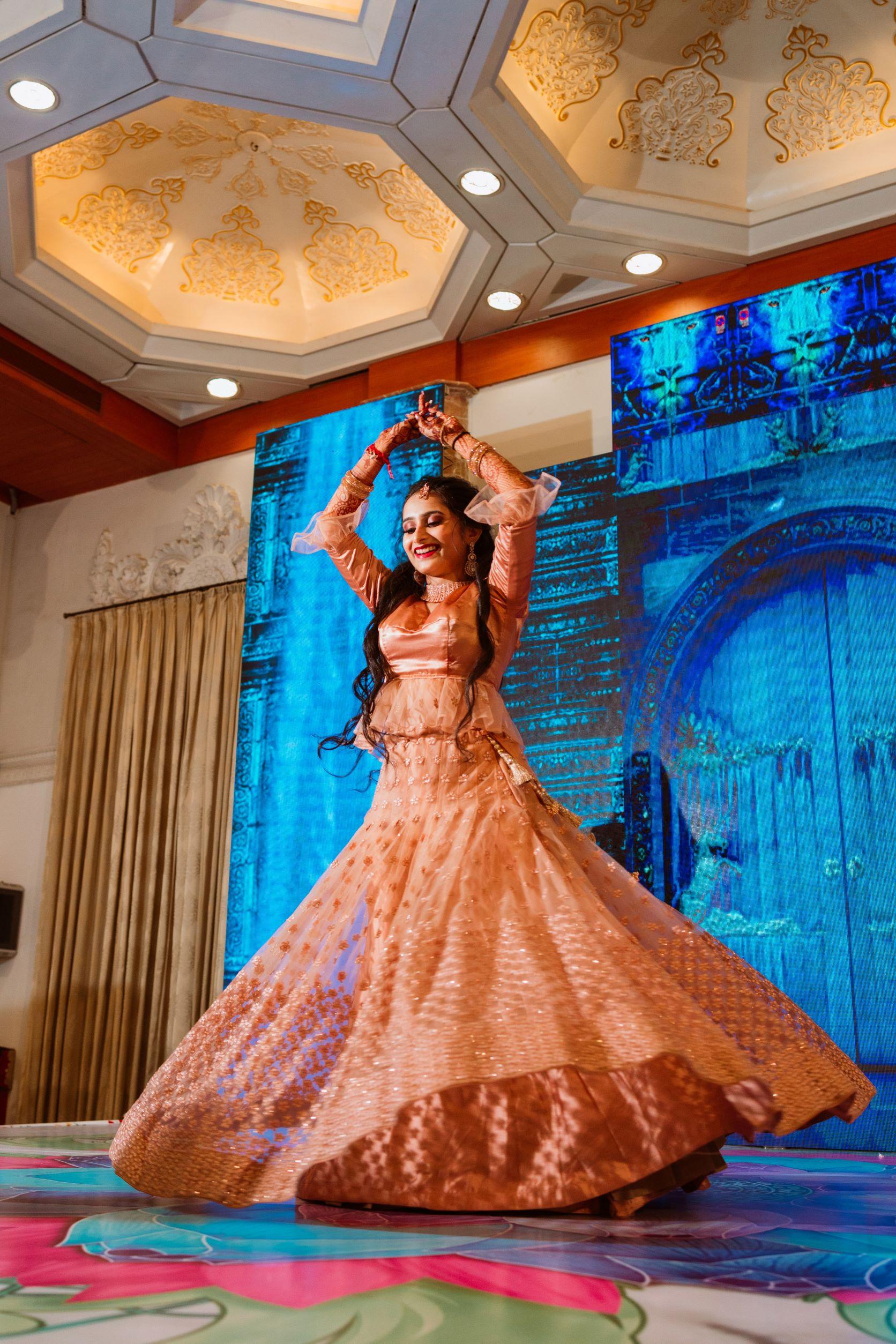 bride dances in peach lehenga