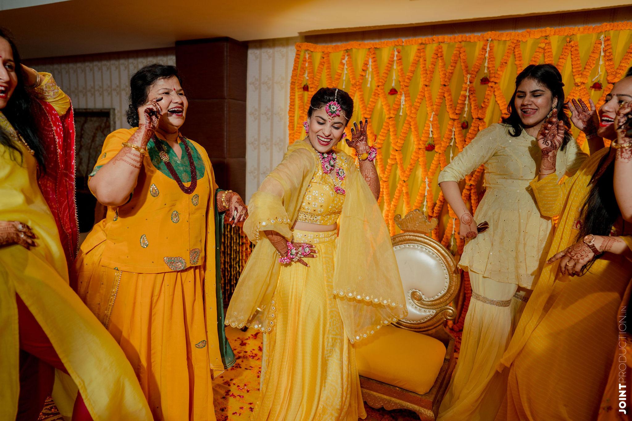 bride dancing in yellow lehenga for haldi