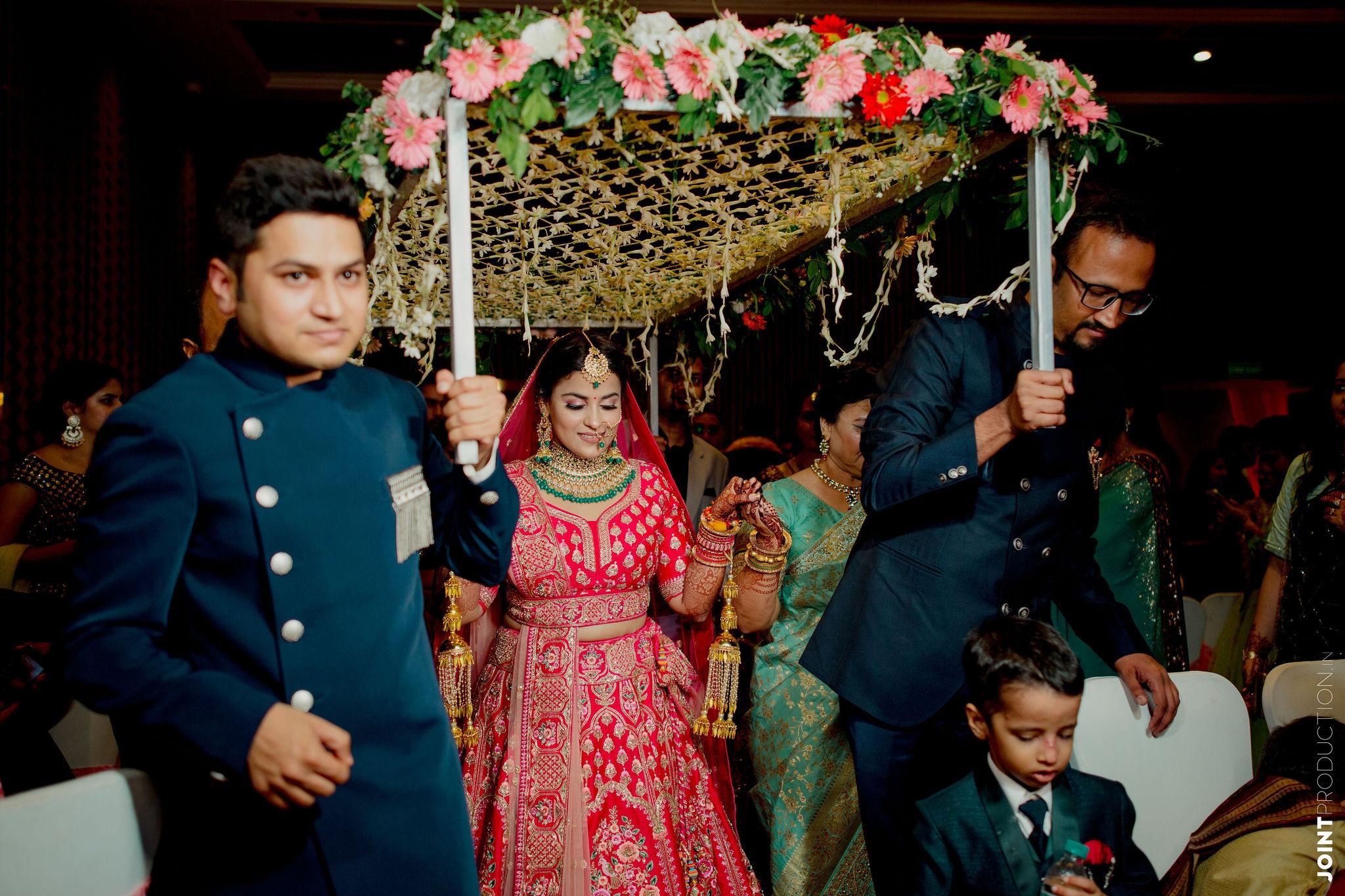 bride enters under a floral chhatri