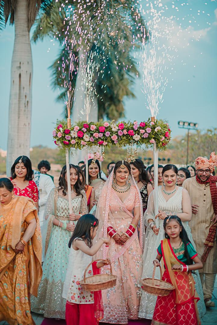 bride enters under a floral chhatro
