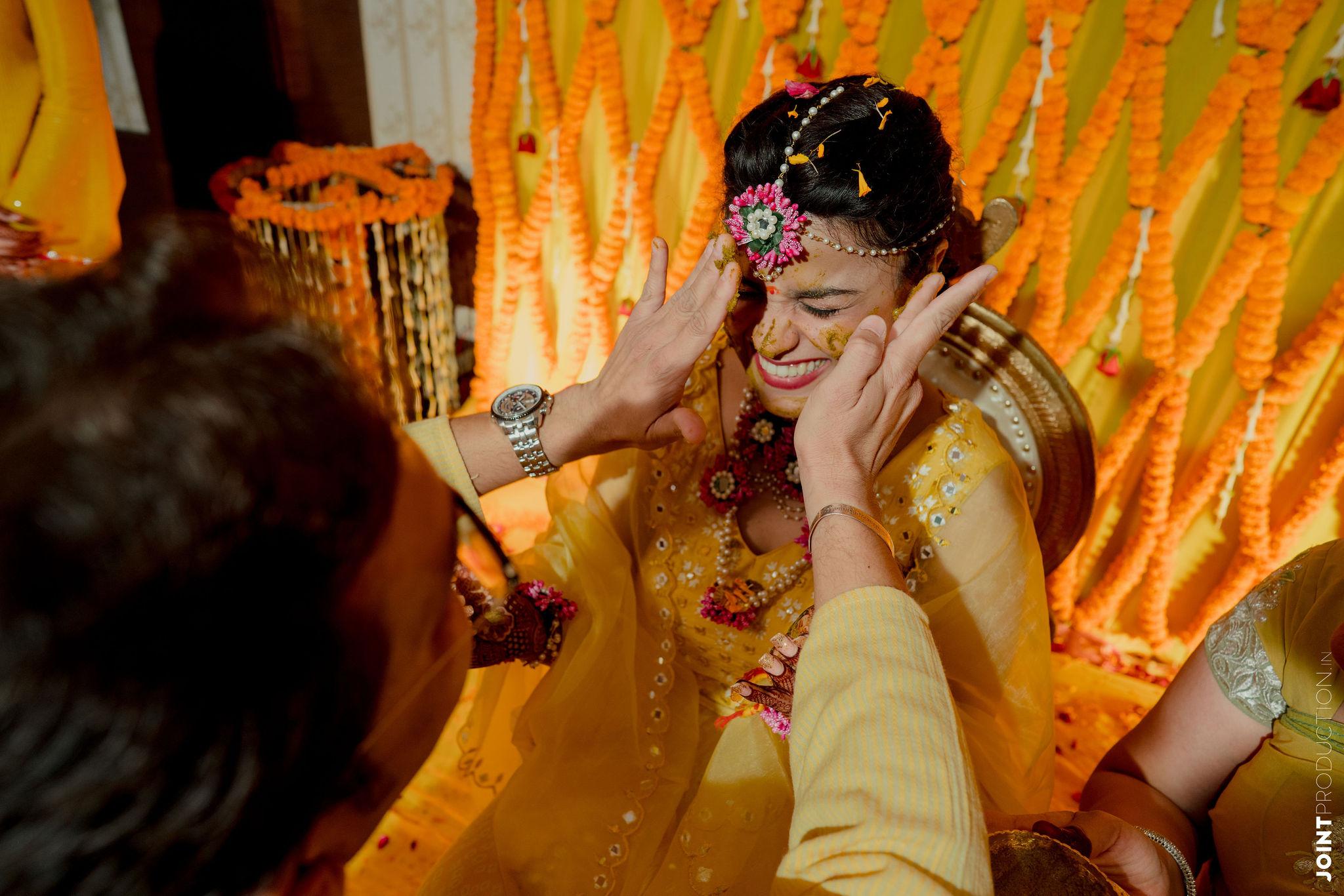 bride getting haldi on her face