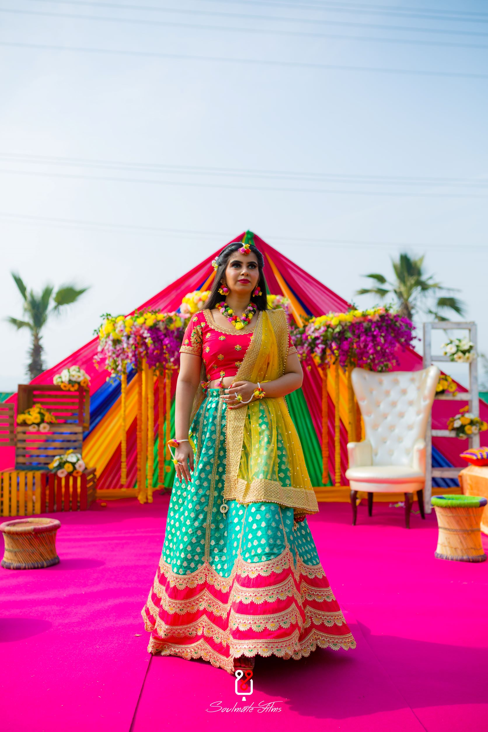 bride in multi coloured lehenga and floral jewellery