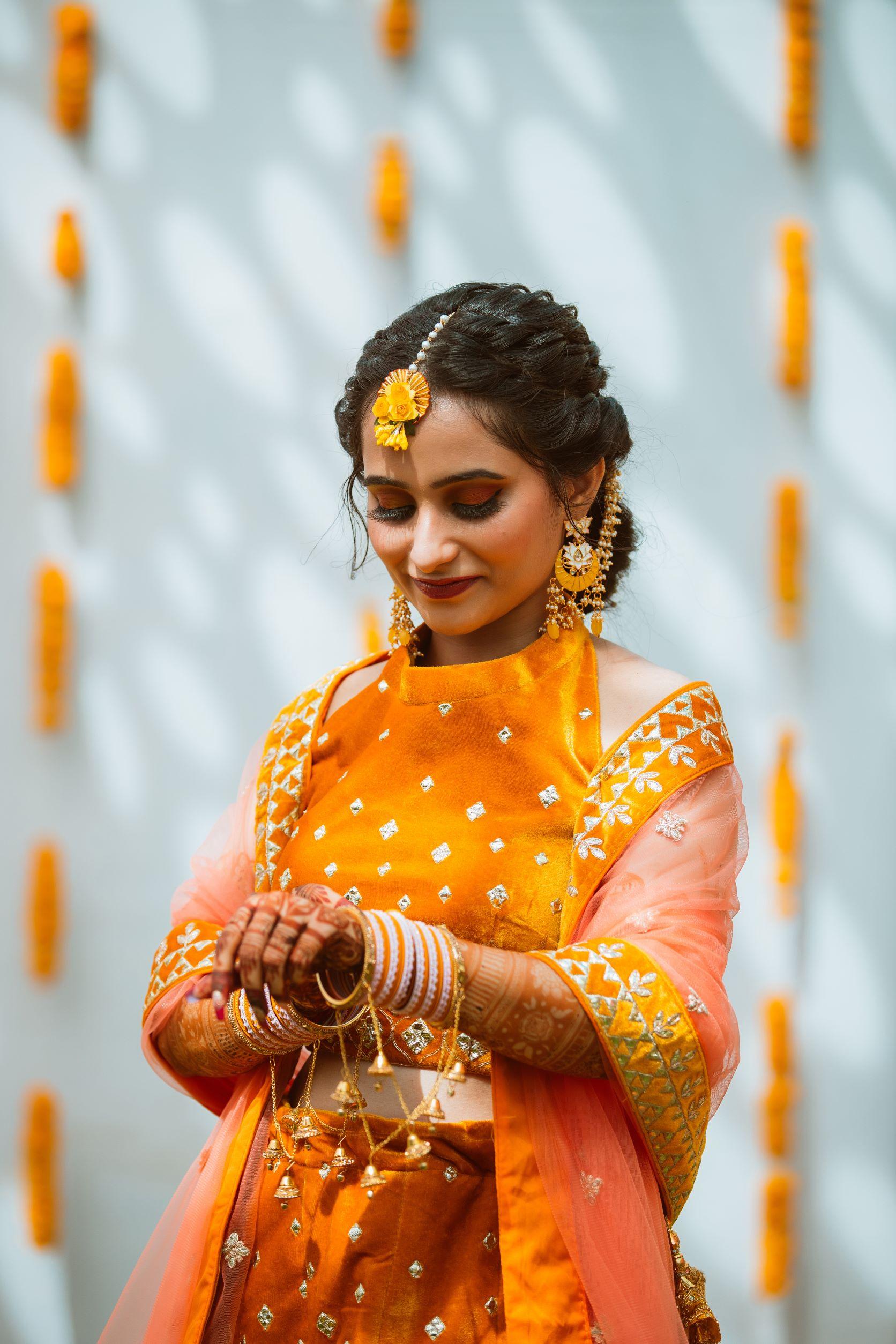 bride in orange lehenga for haldi