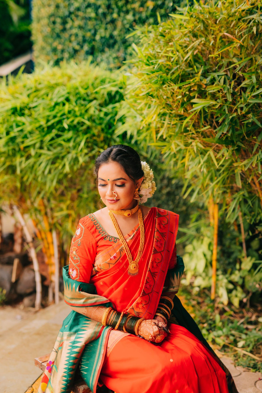 bride in orange paithani saree