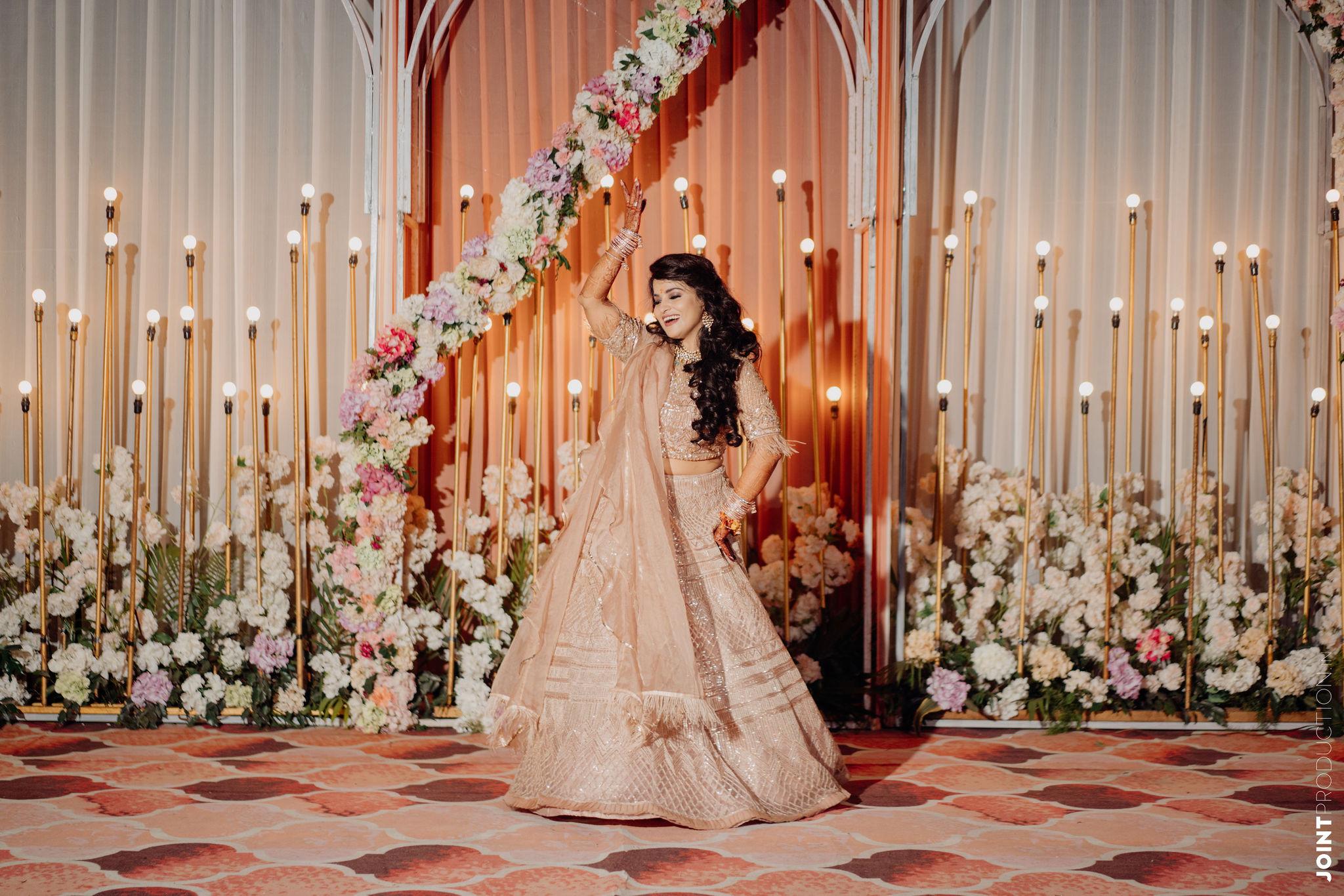 bride in pastel lehenga dancing