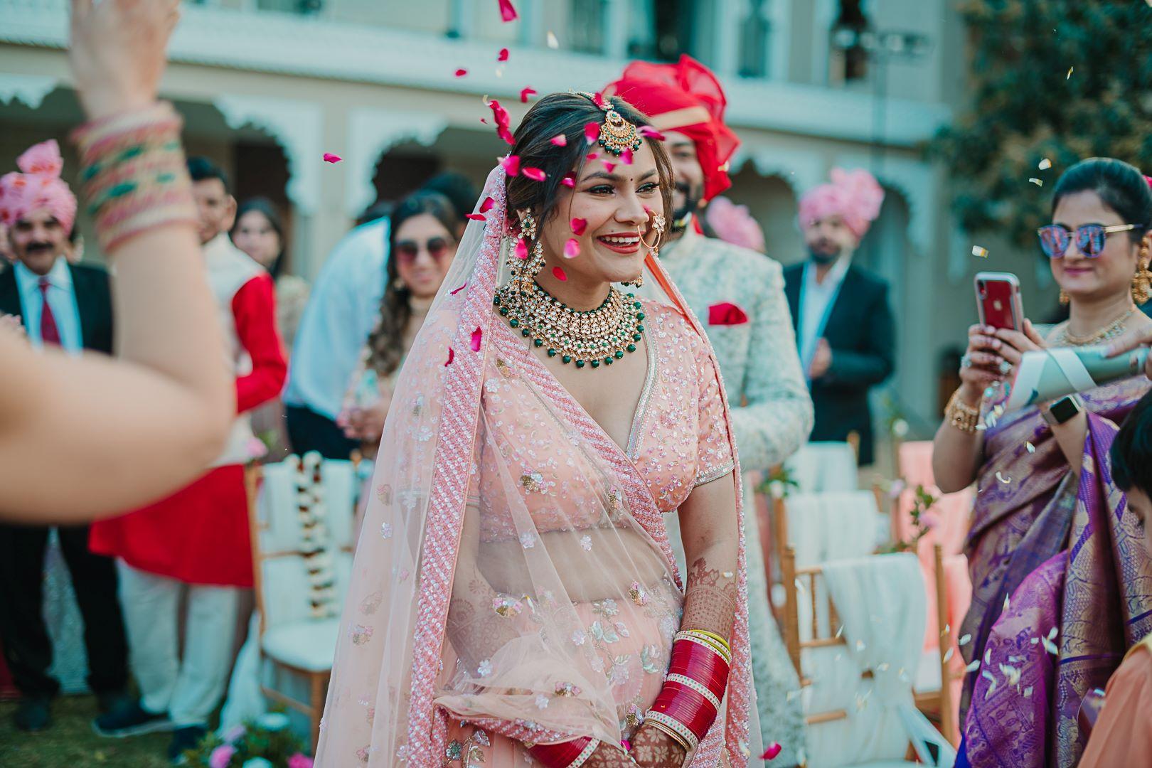bride in peach bridal lehenga and contrasting bridal jewellery