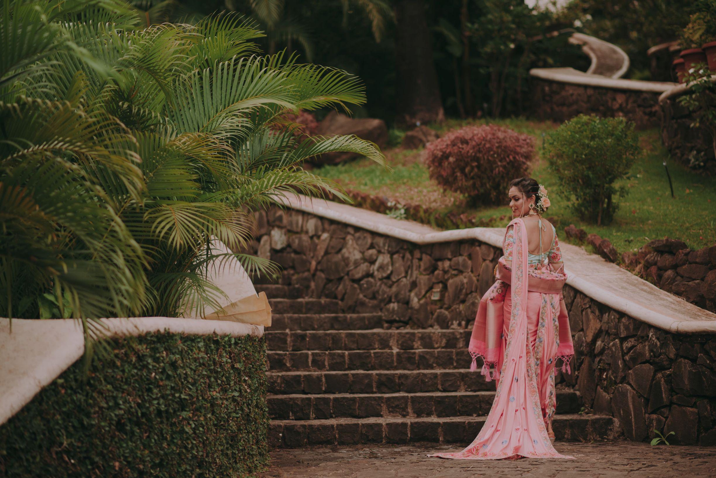 bride in pink saree and floral bridal bun