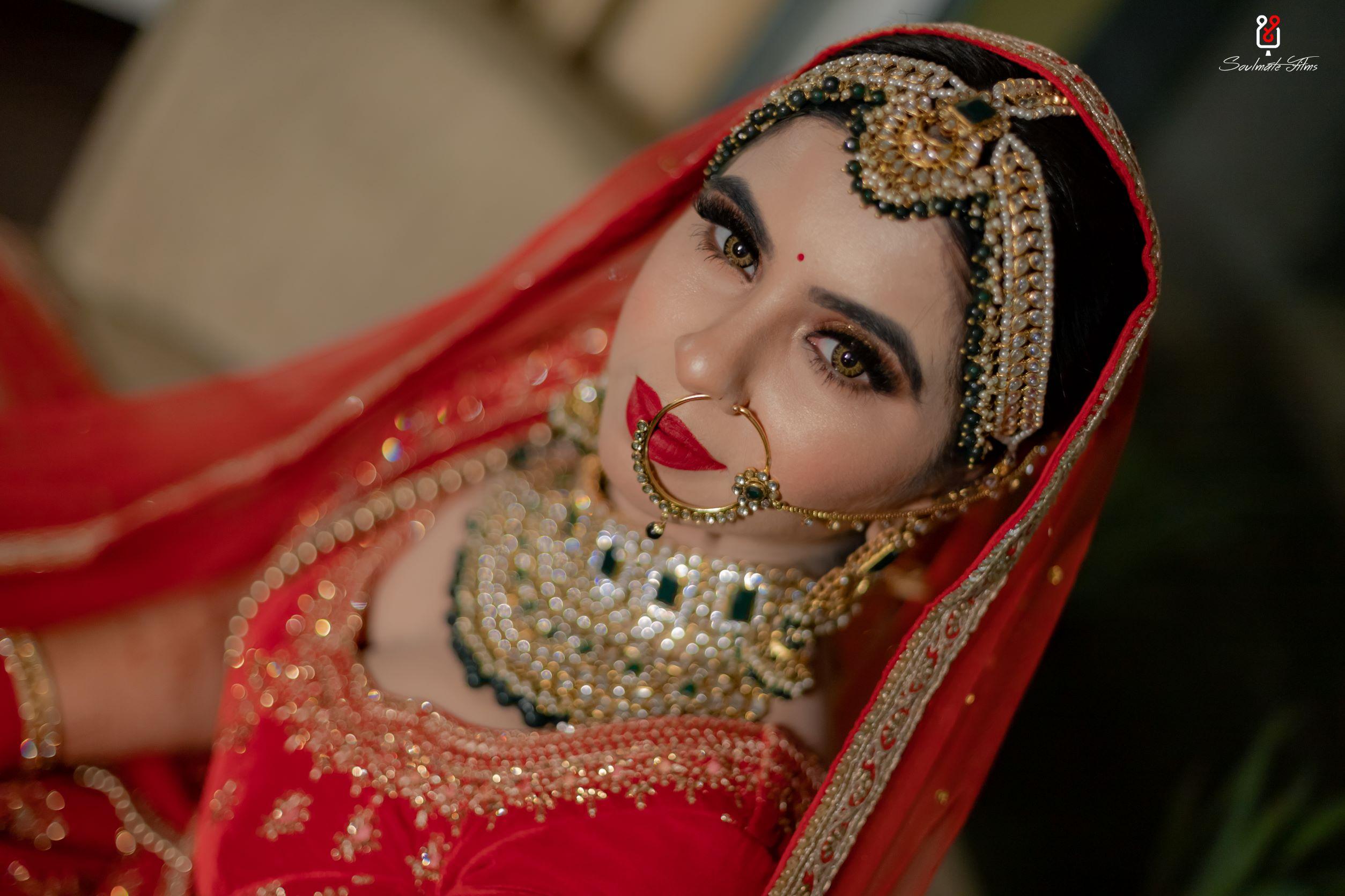 bride in red bridal lehenga and contrasting bridal jewellery