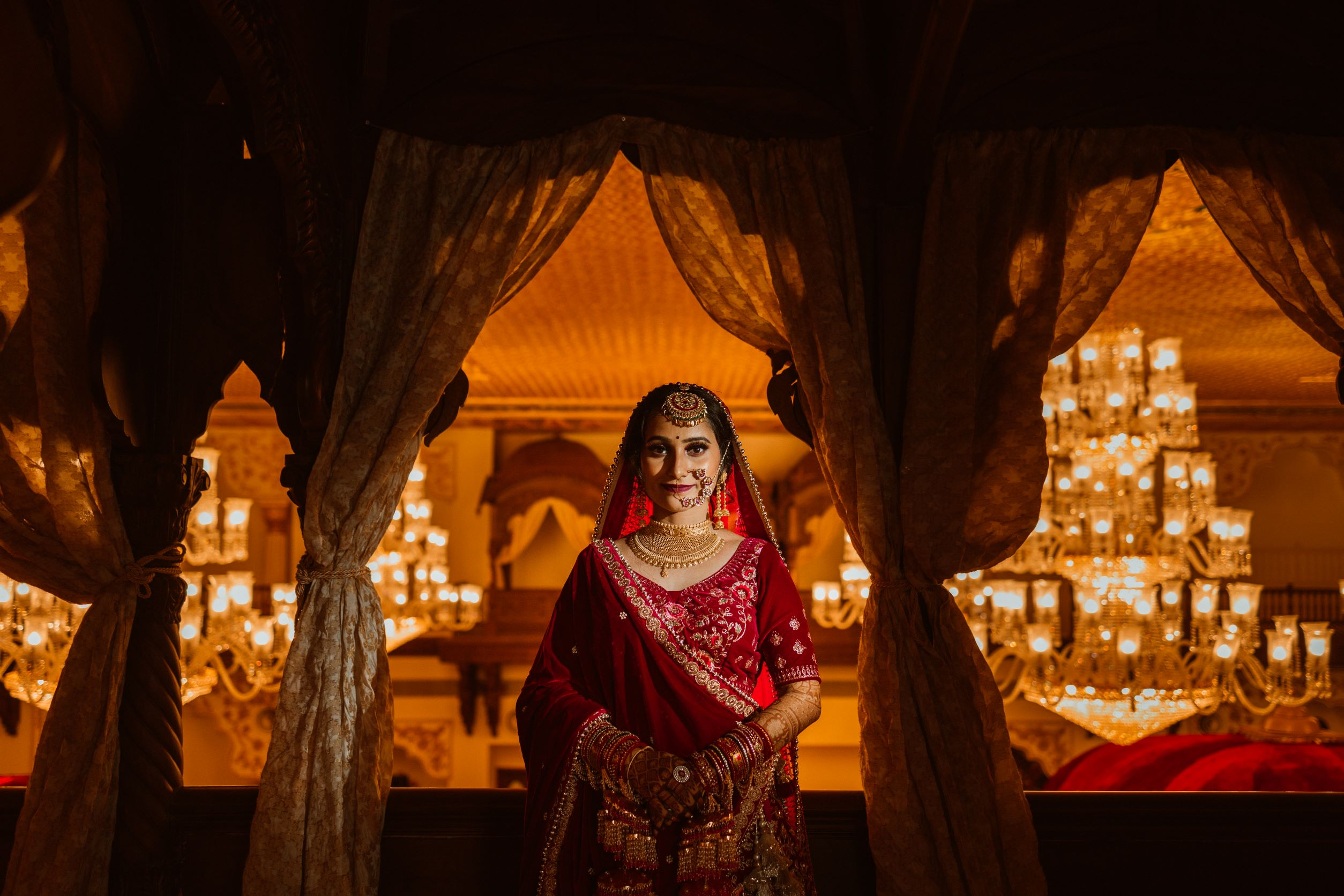 bride in red bridal lehenga and gold bridal jewellery