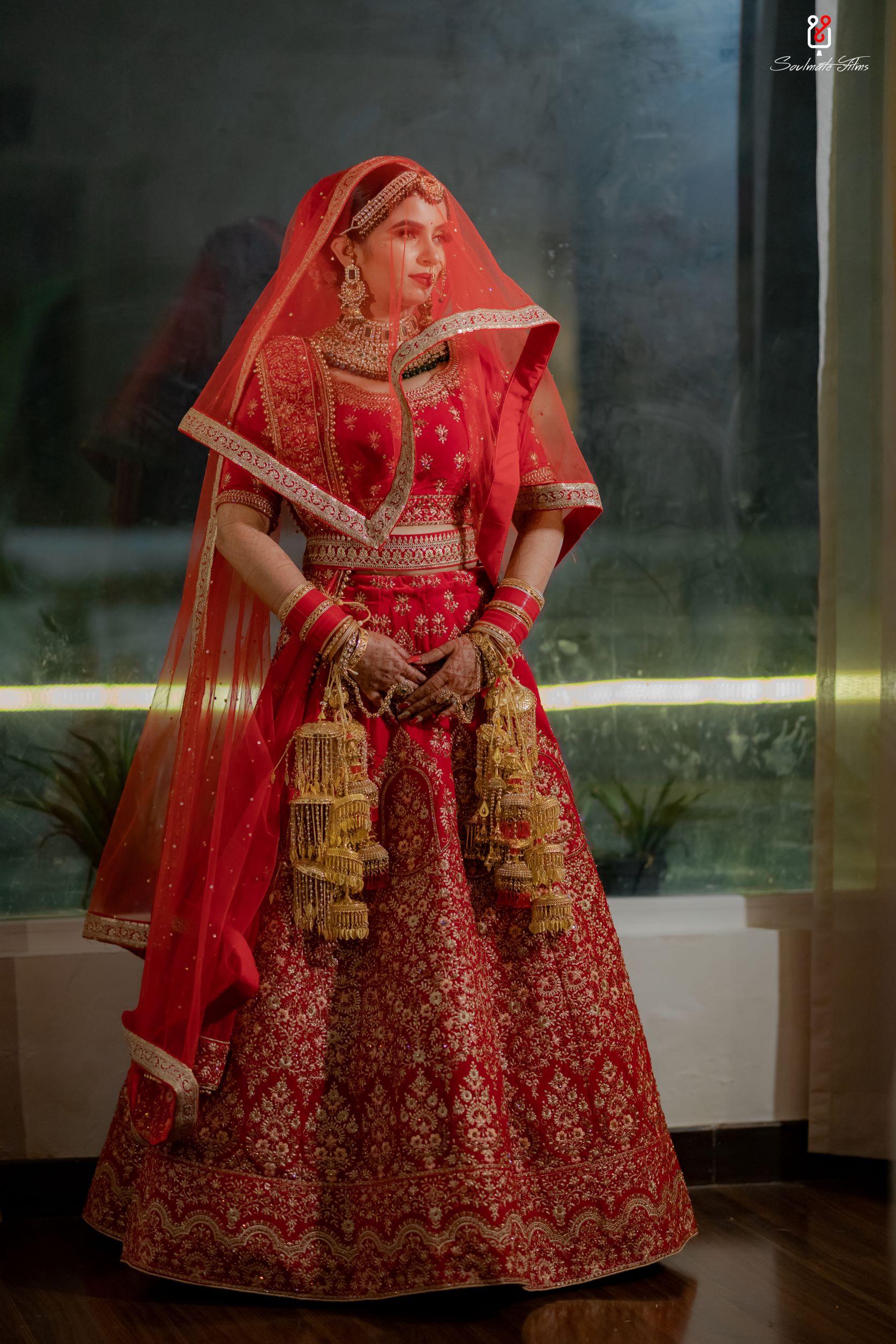 bride in red bridal lehenga and gold bridal kalire