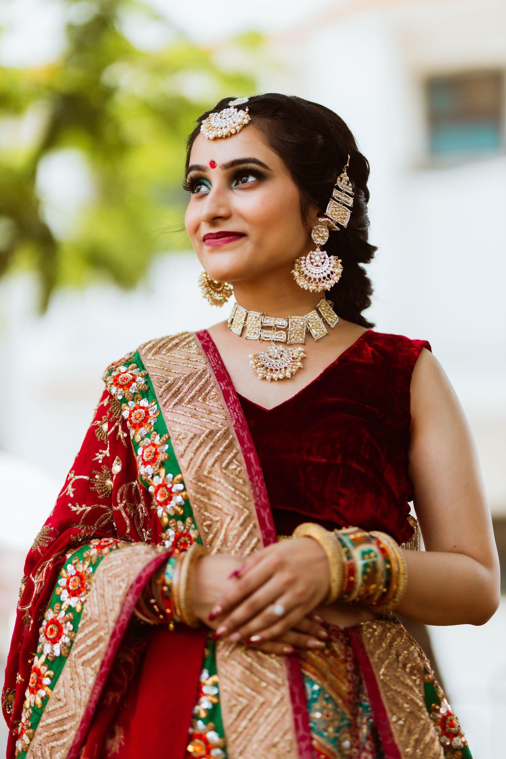 bride in red bridal lehenga and kundan jewellery