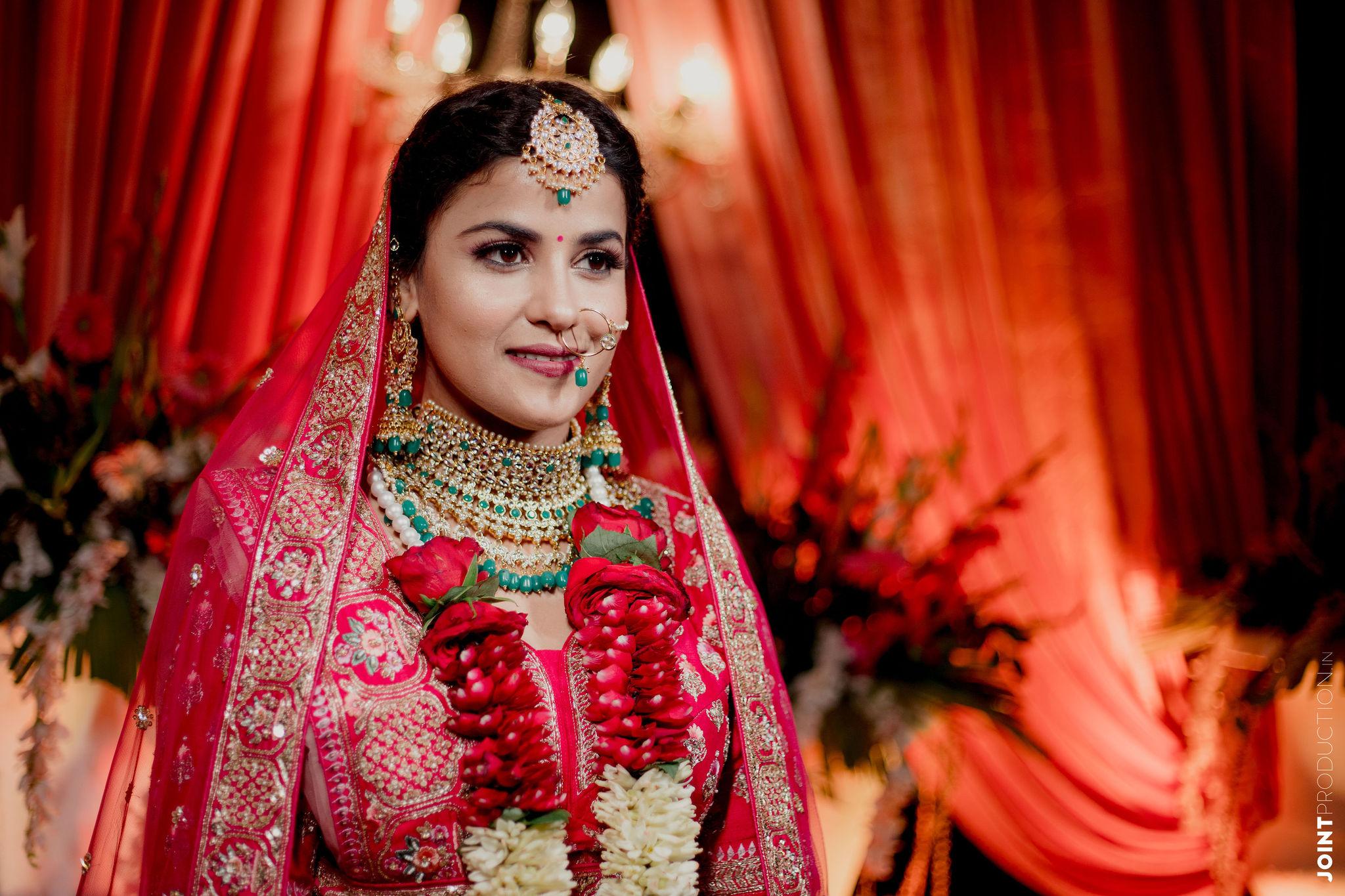 bride in red bridal lehenga and rose jaimala