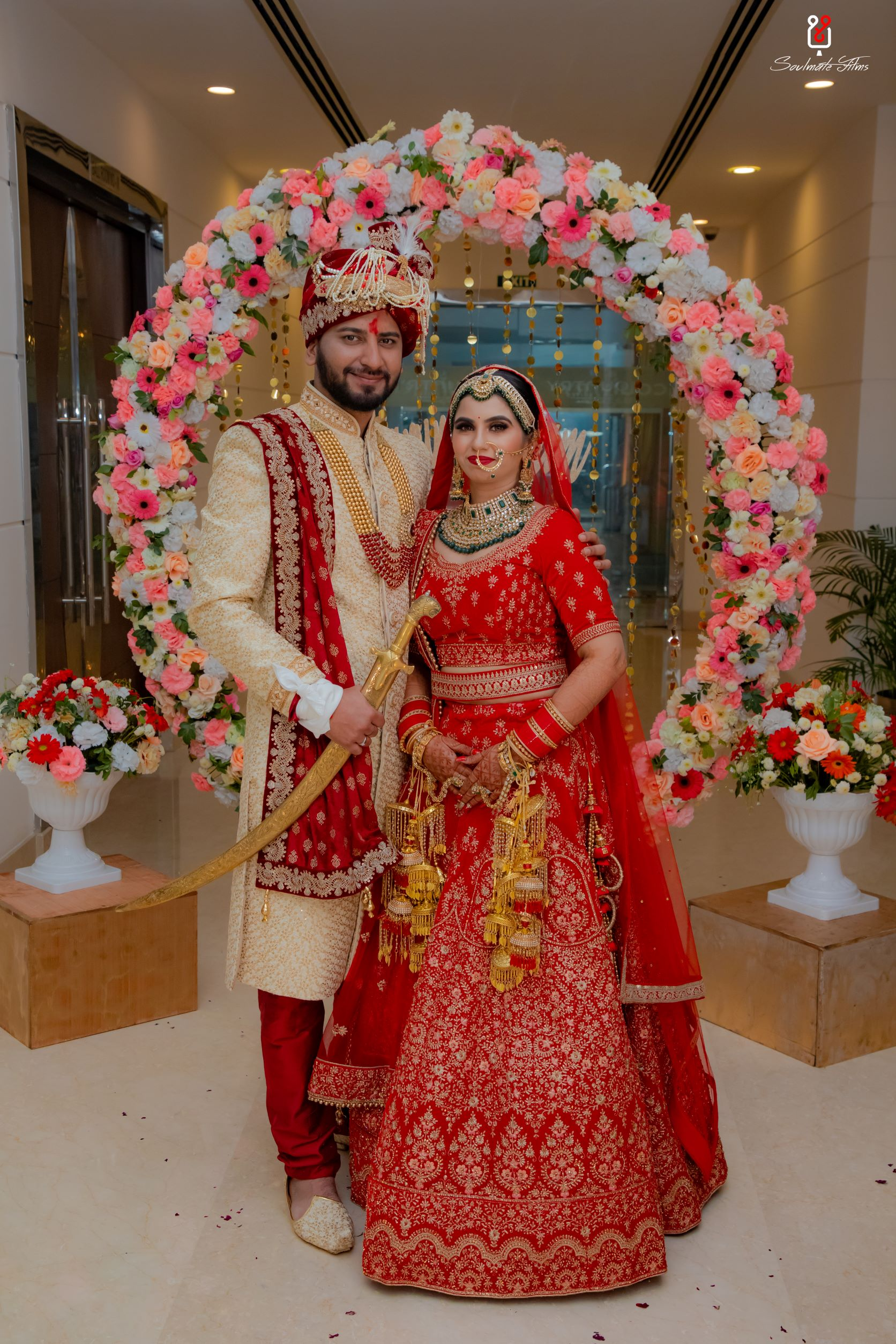 bride in red bridal lehenga poses with her groom