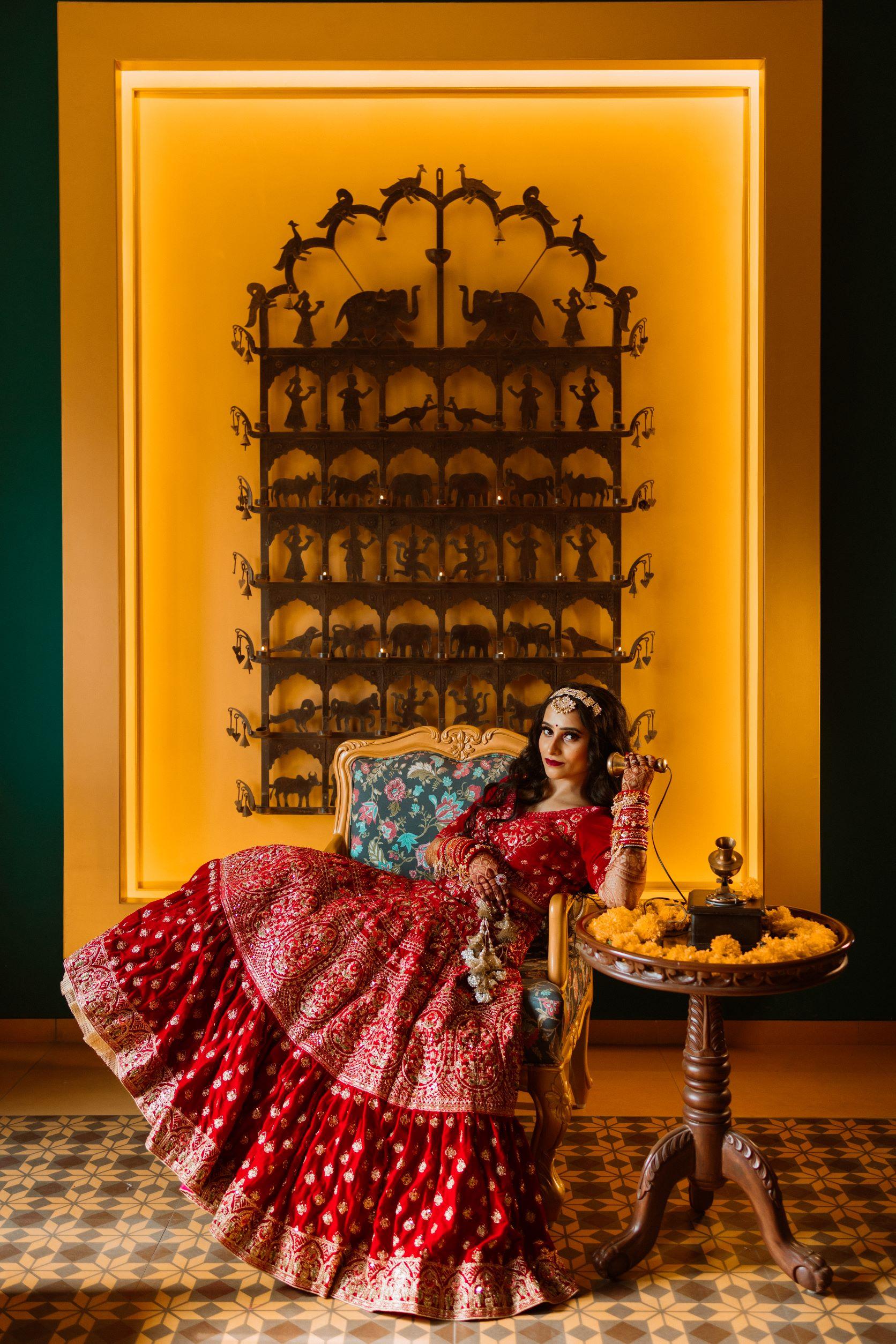 bride in red bridal lehenga poses with vintage phone
