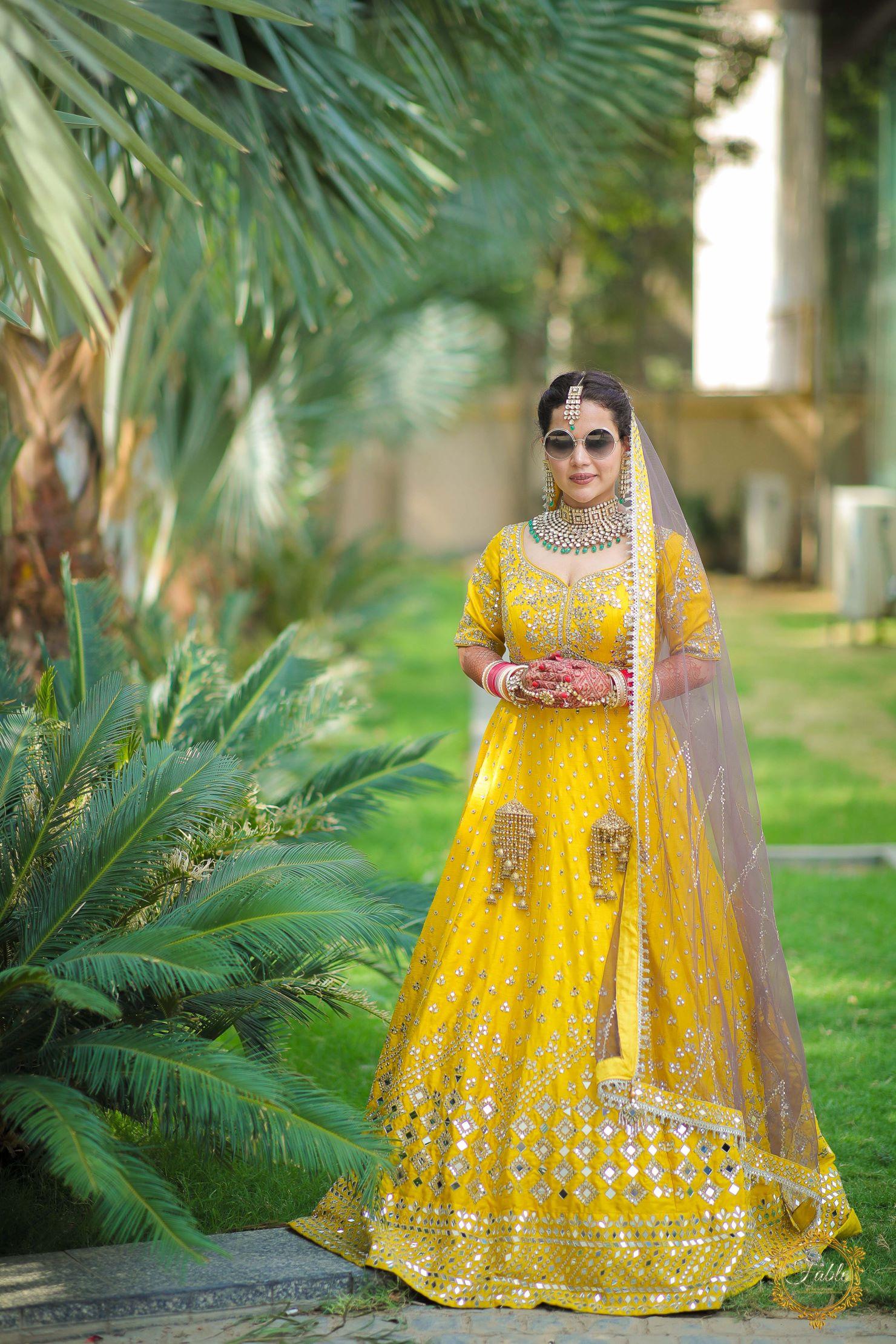 bride in yellow bridal lehenga and shades