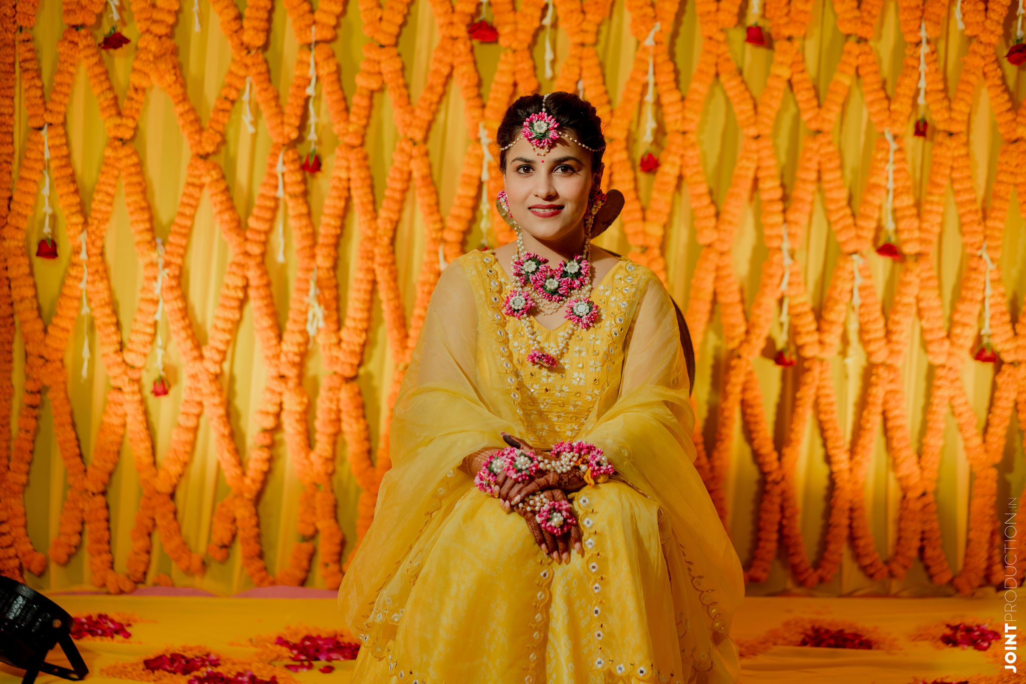 bride in yellow lehenga and floral jewellery