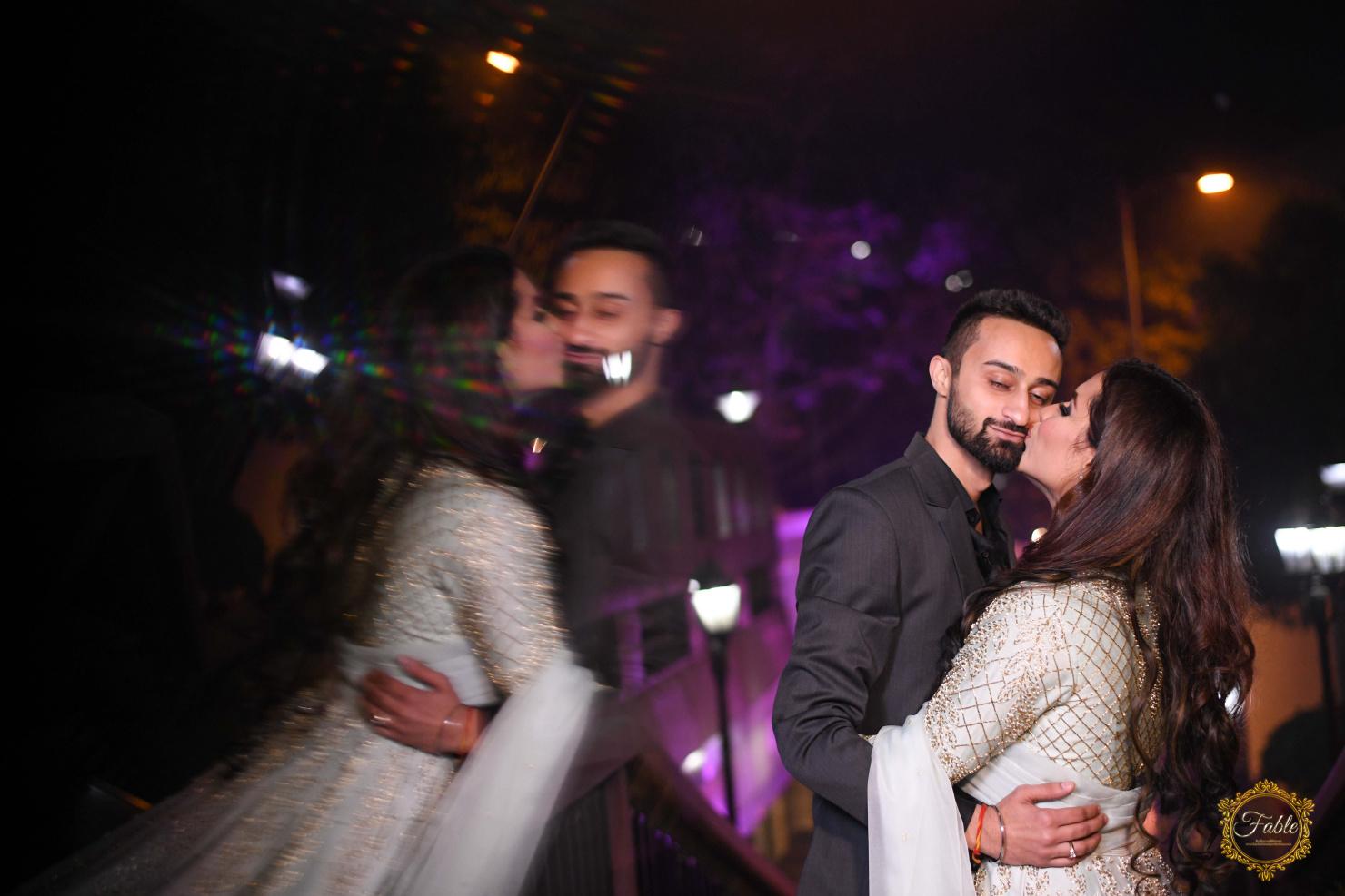 bride kissing on groom's cheeks