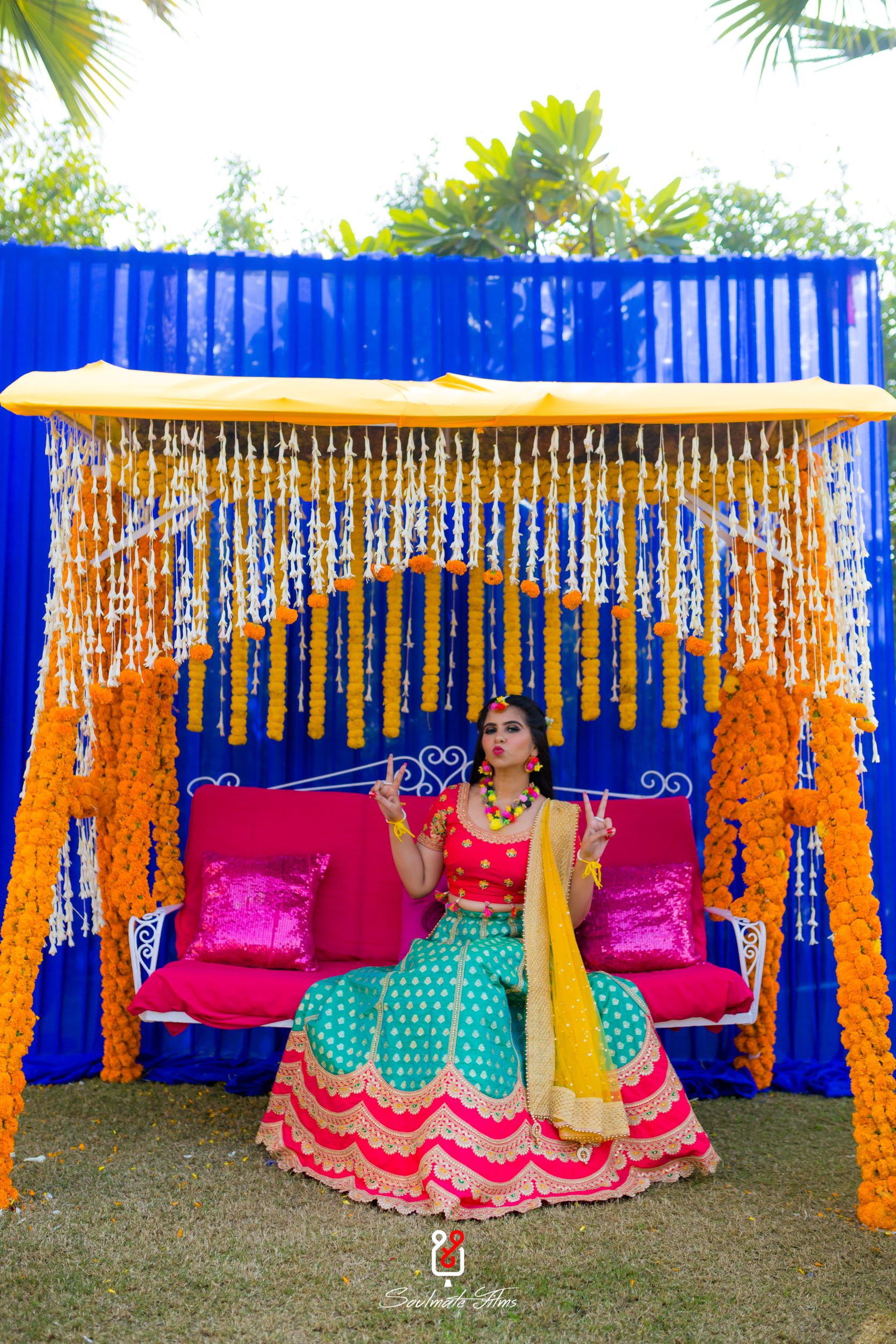 bride poses on a marigold decorated swing