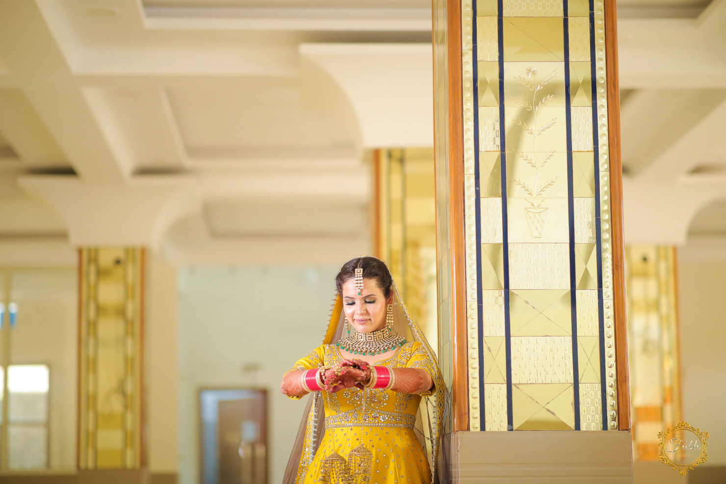 bride poses with her red bridal chooda