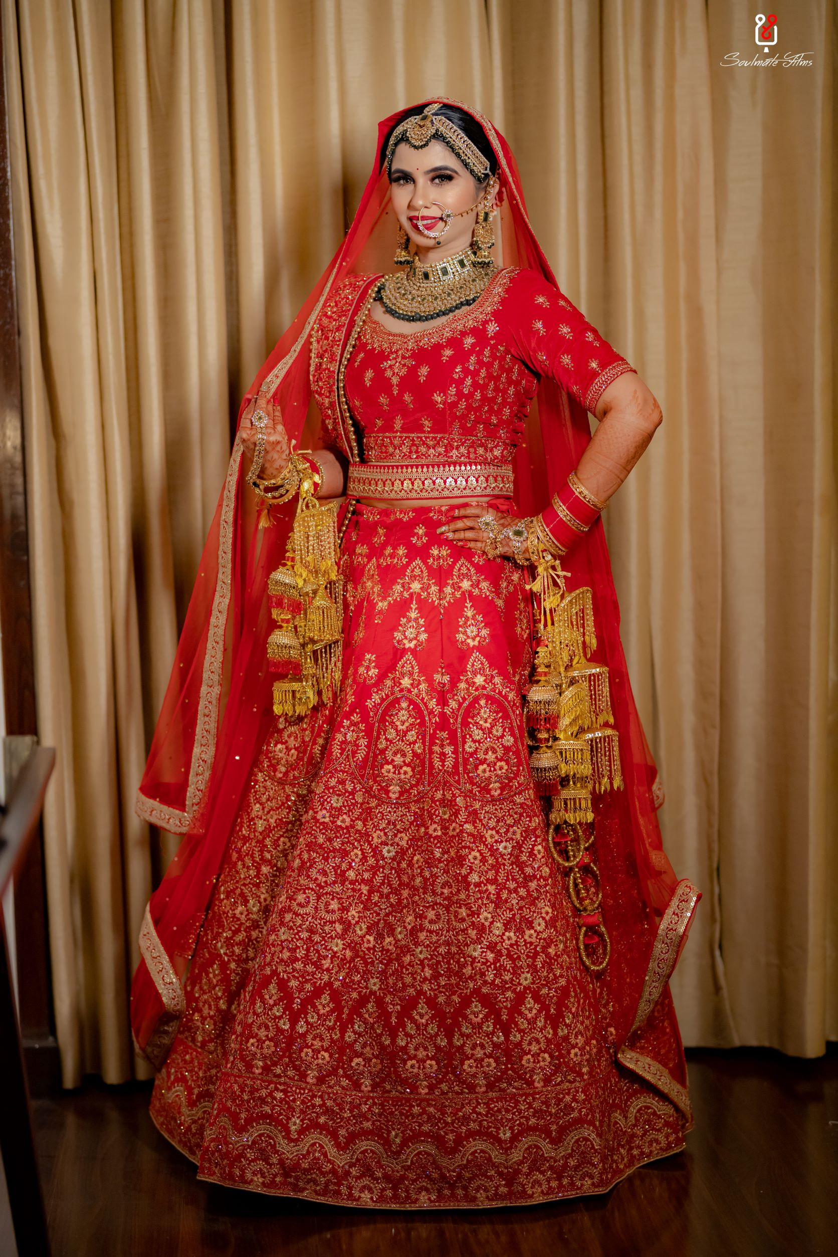 bride poses with her red bridal dupatta