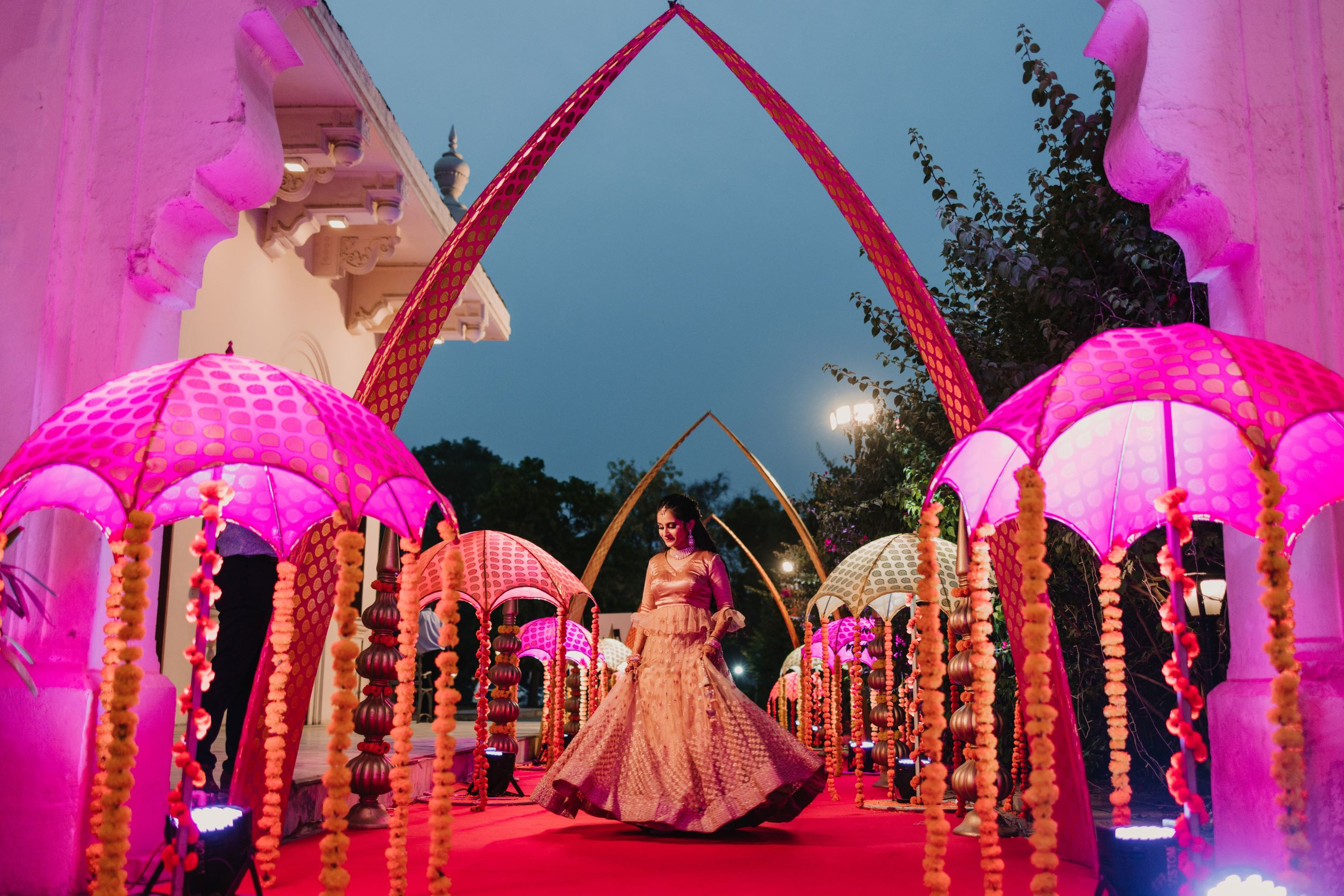 bride poses with pink sangeet decor