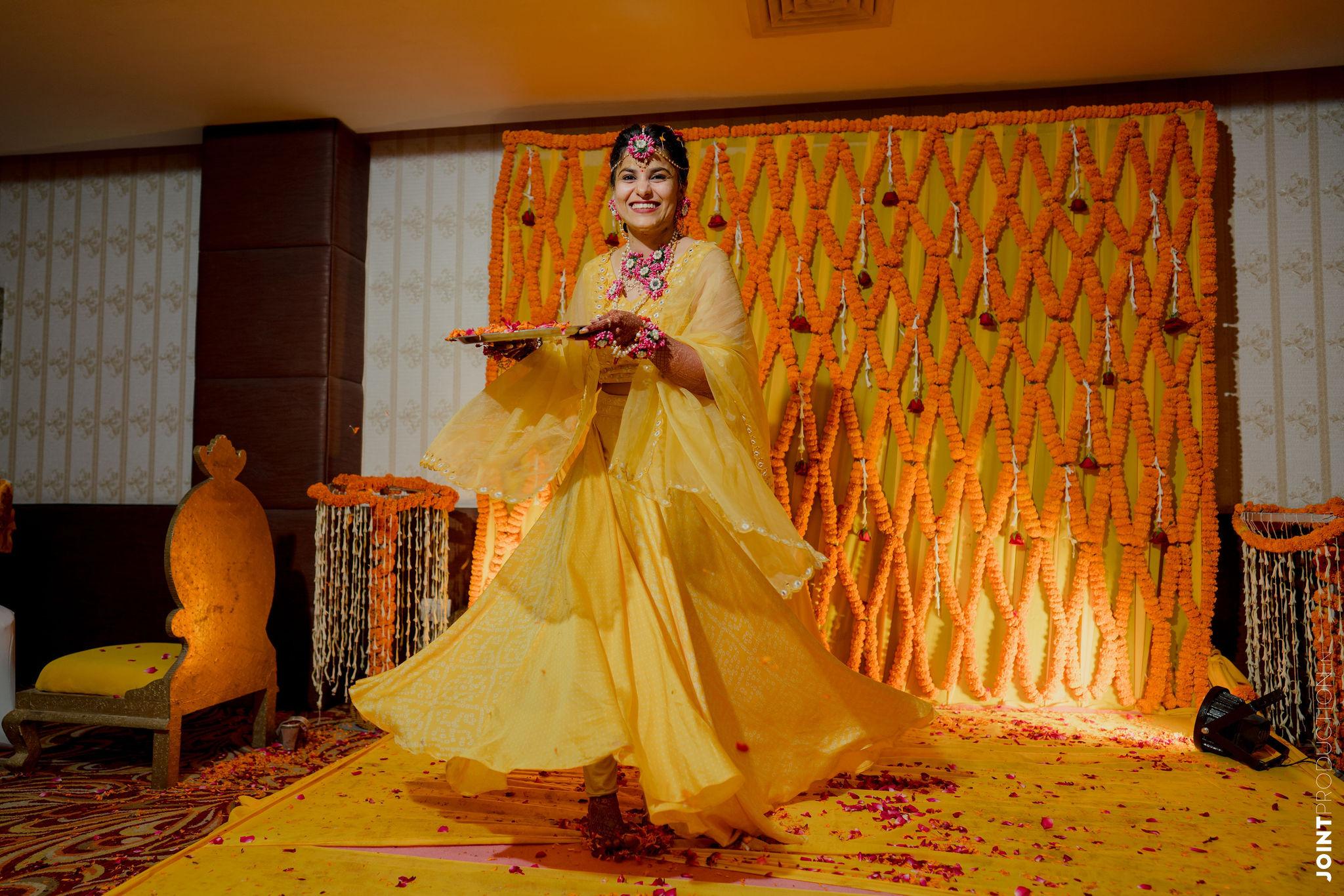 bride twirling in yellow lehenga for haldi