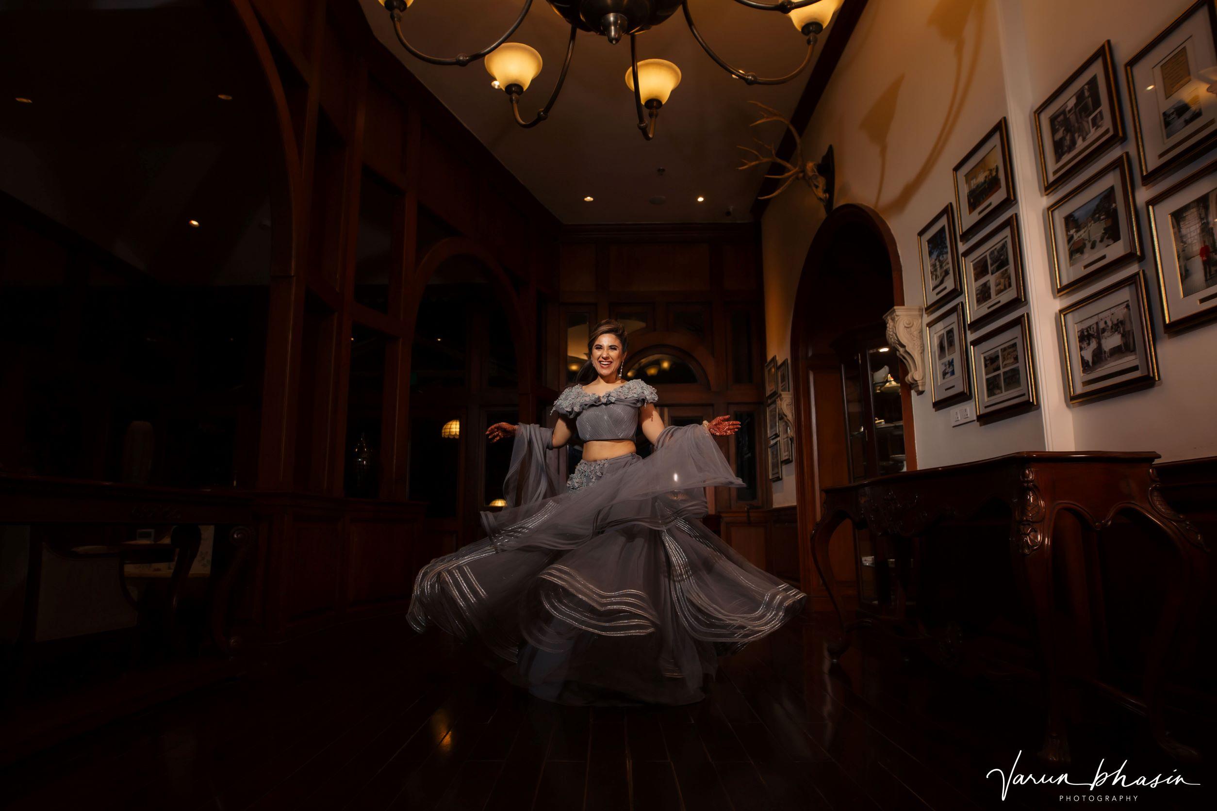 bride twirls in her grey lehenga