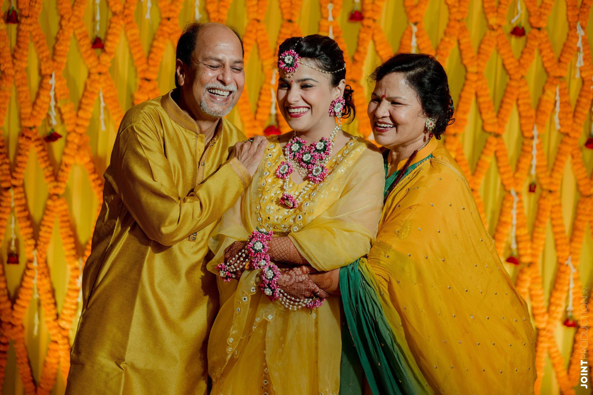 bride with her parents at her haldi