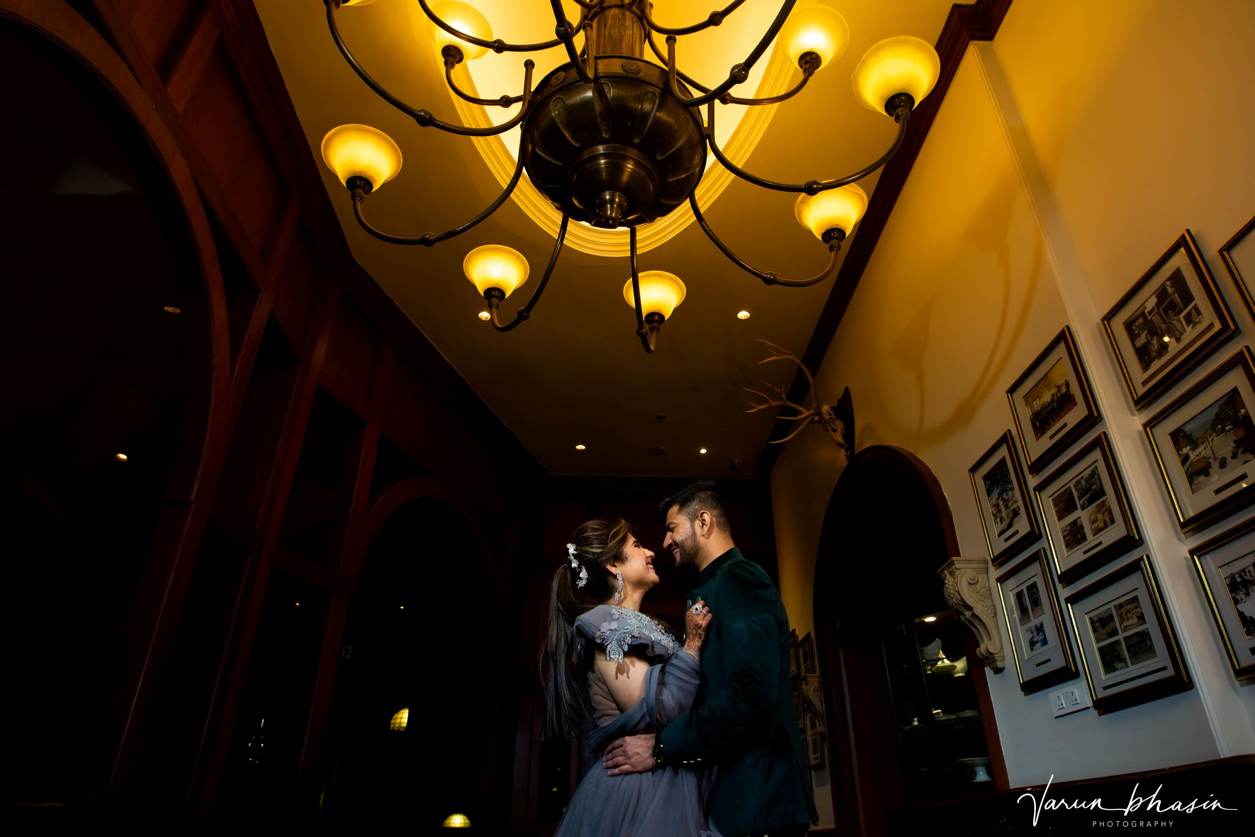 candid shot of the couple under a chandeliar
