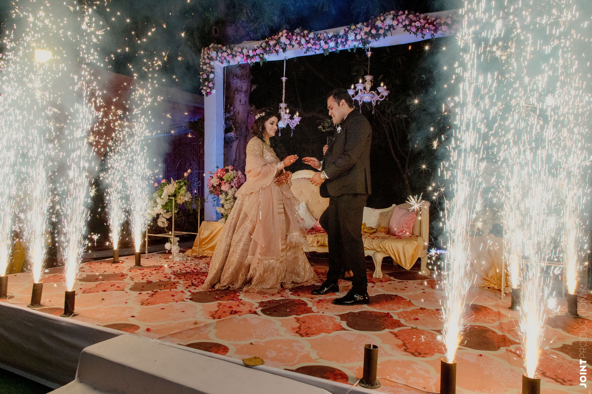 couple exchanging rings amongst fireworks