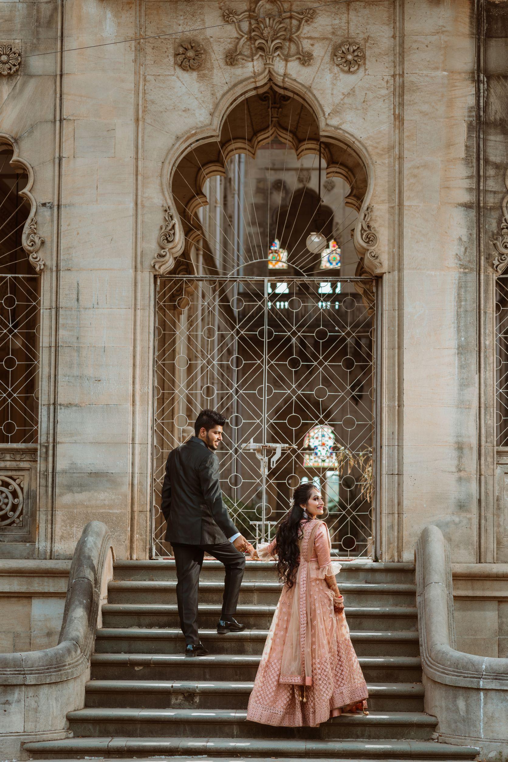groom in black suit and bride in peach lehenga.