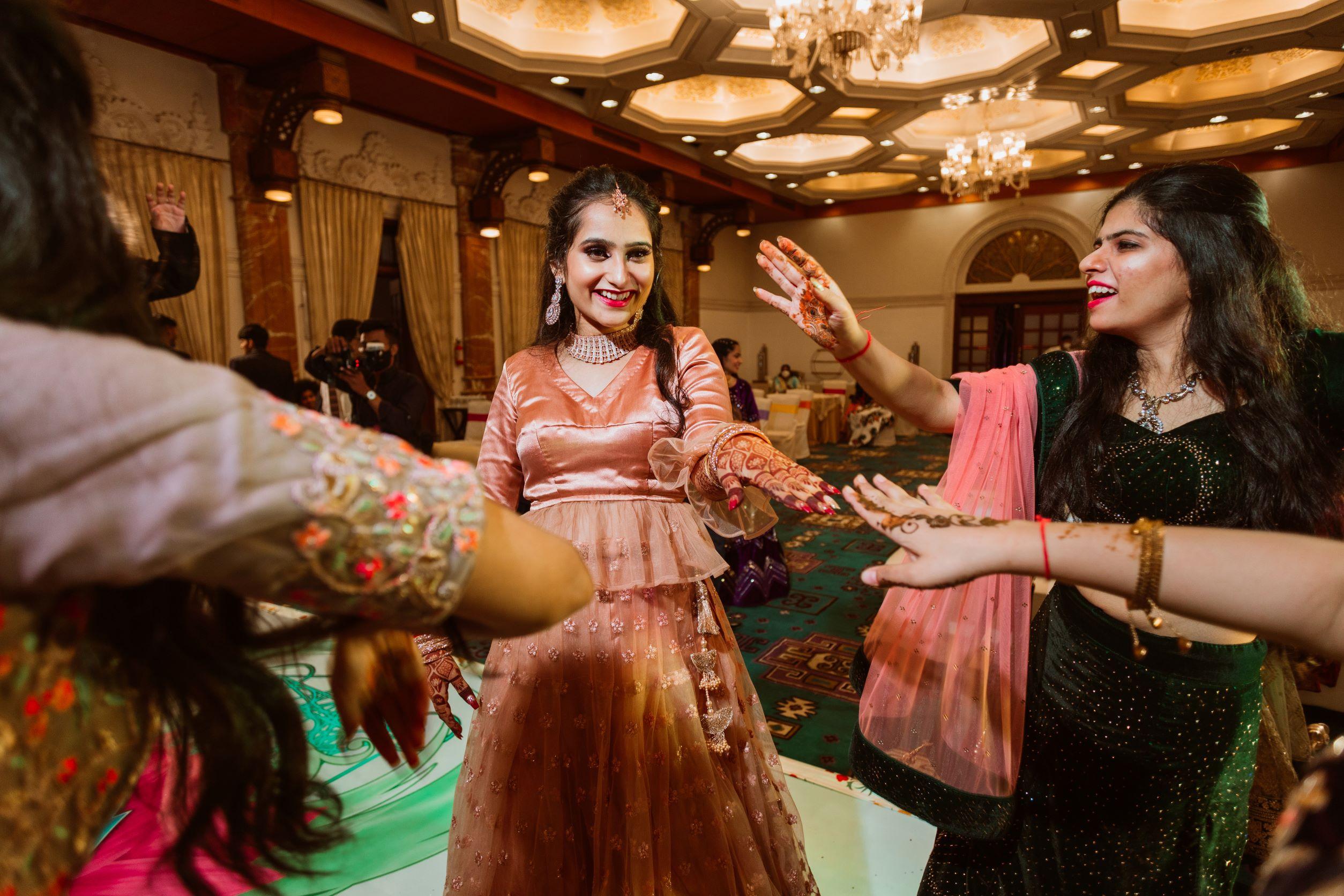 happy bride dances with her bridesmaids