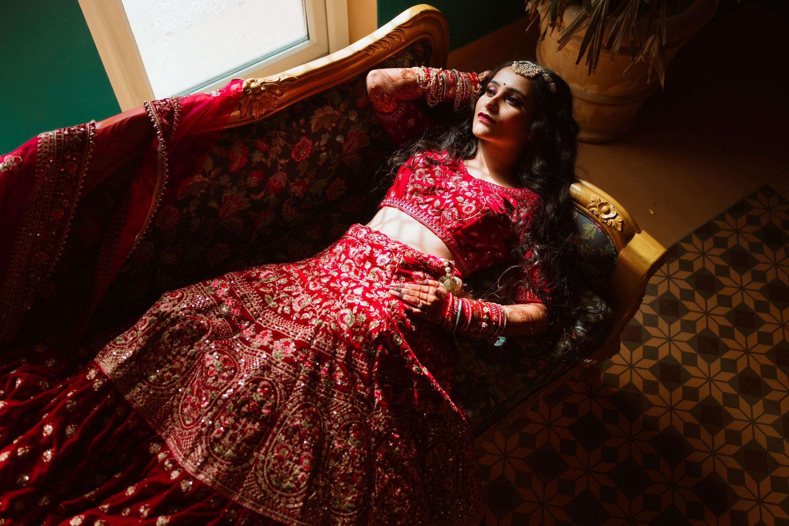 happy bride in floral red bridal lehenga