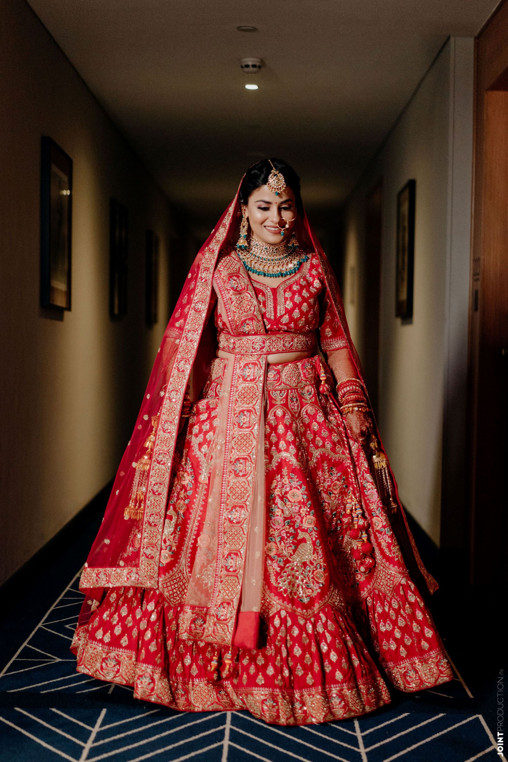 happy bride in red bridal lehenga