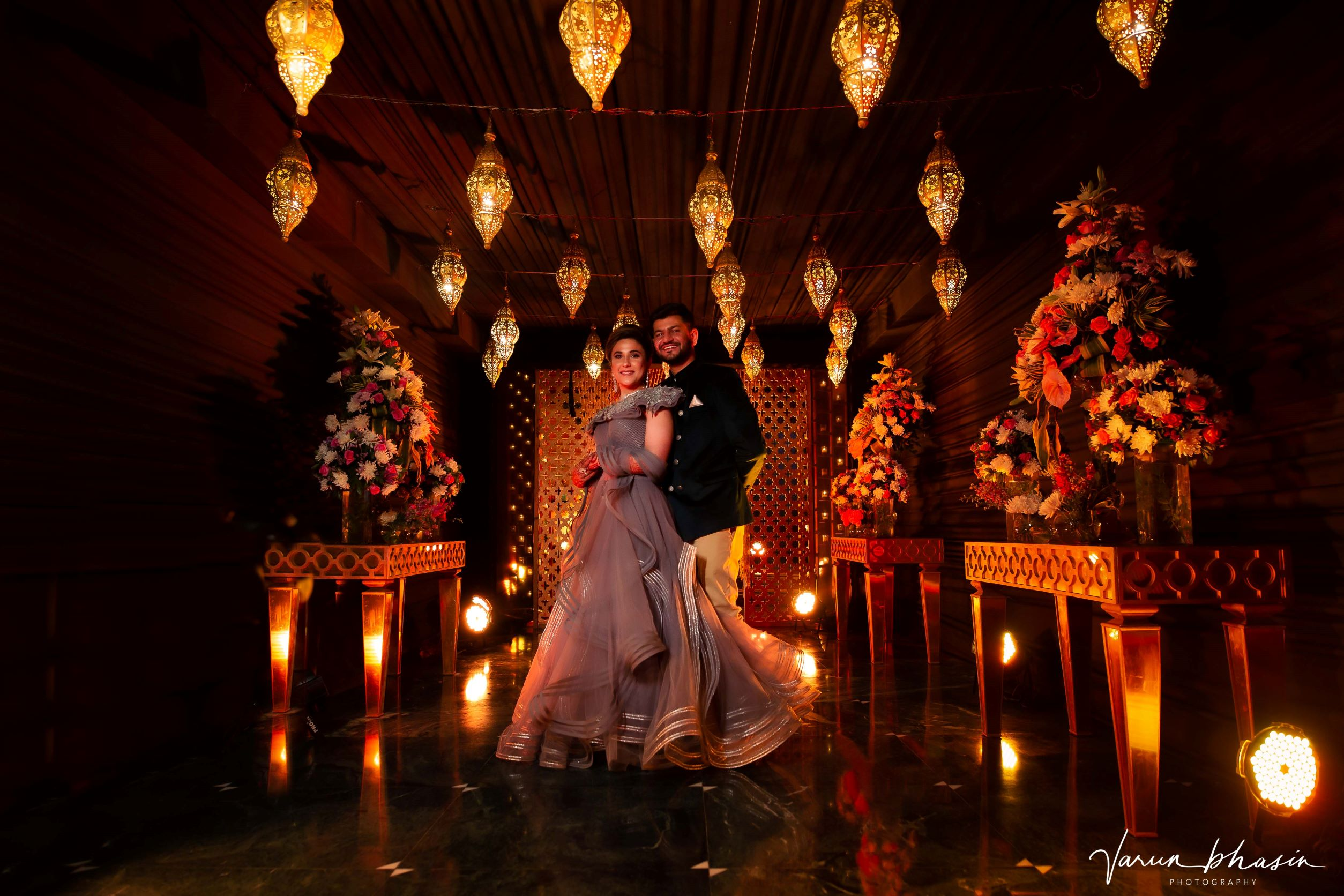 happy couple poses with lit backdrop