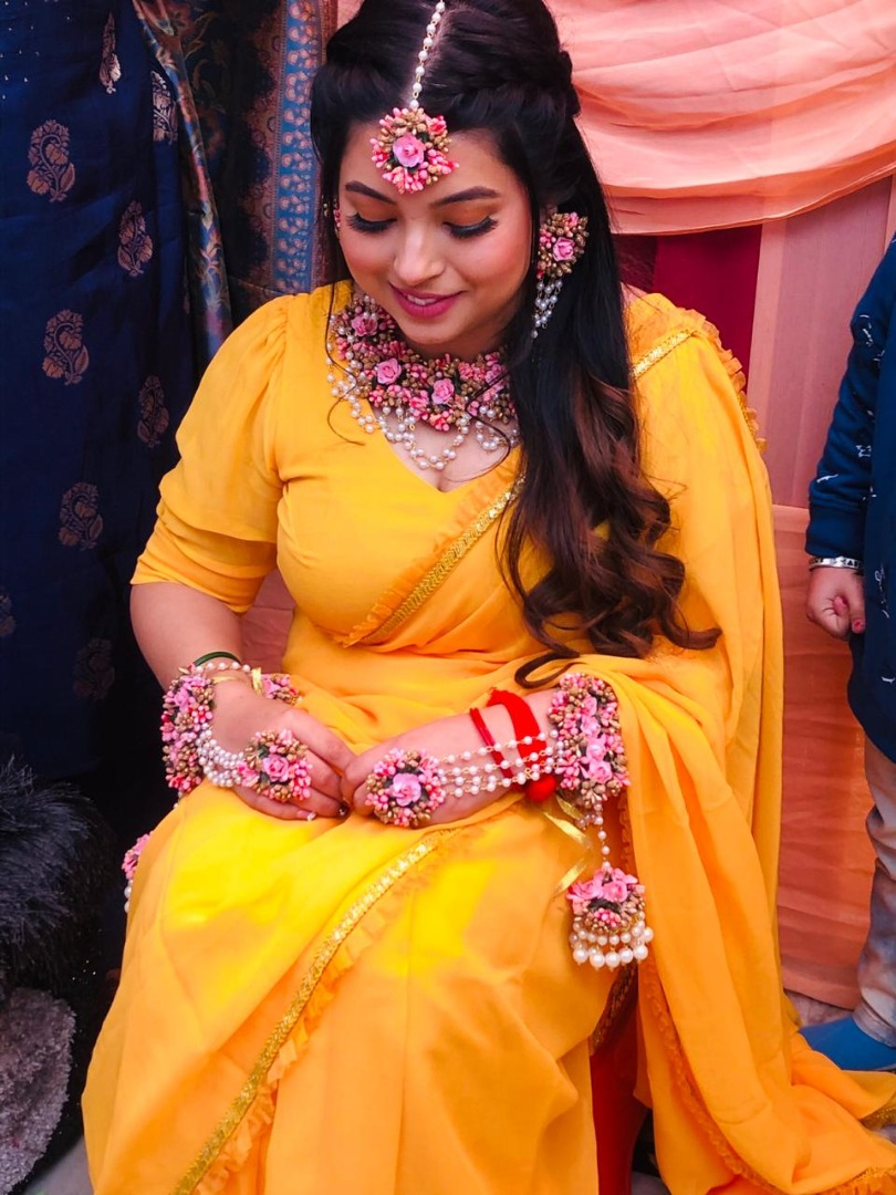bride in a soft nude makeup look and yellow saree