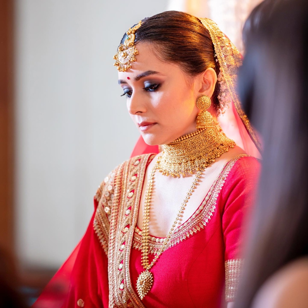 bride in red lehenga and gold jewelry