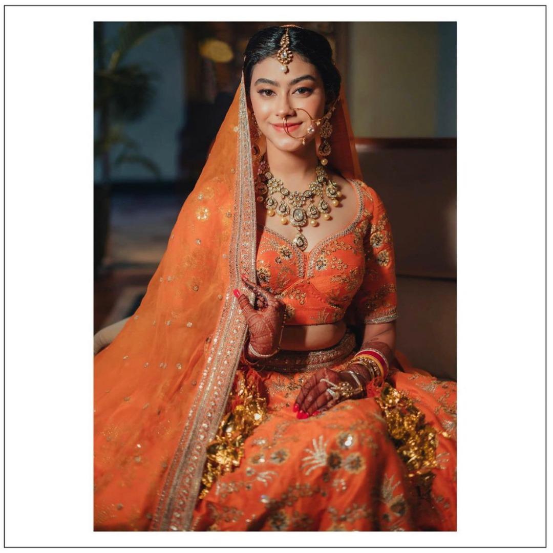 bride in orange lehenga and natural bridal makeup