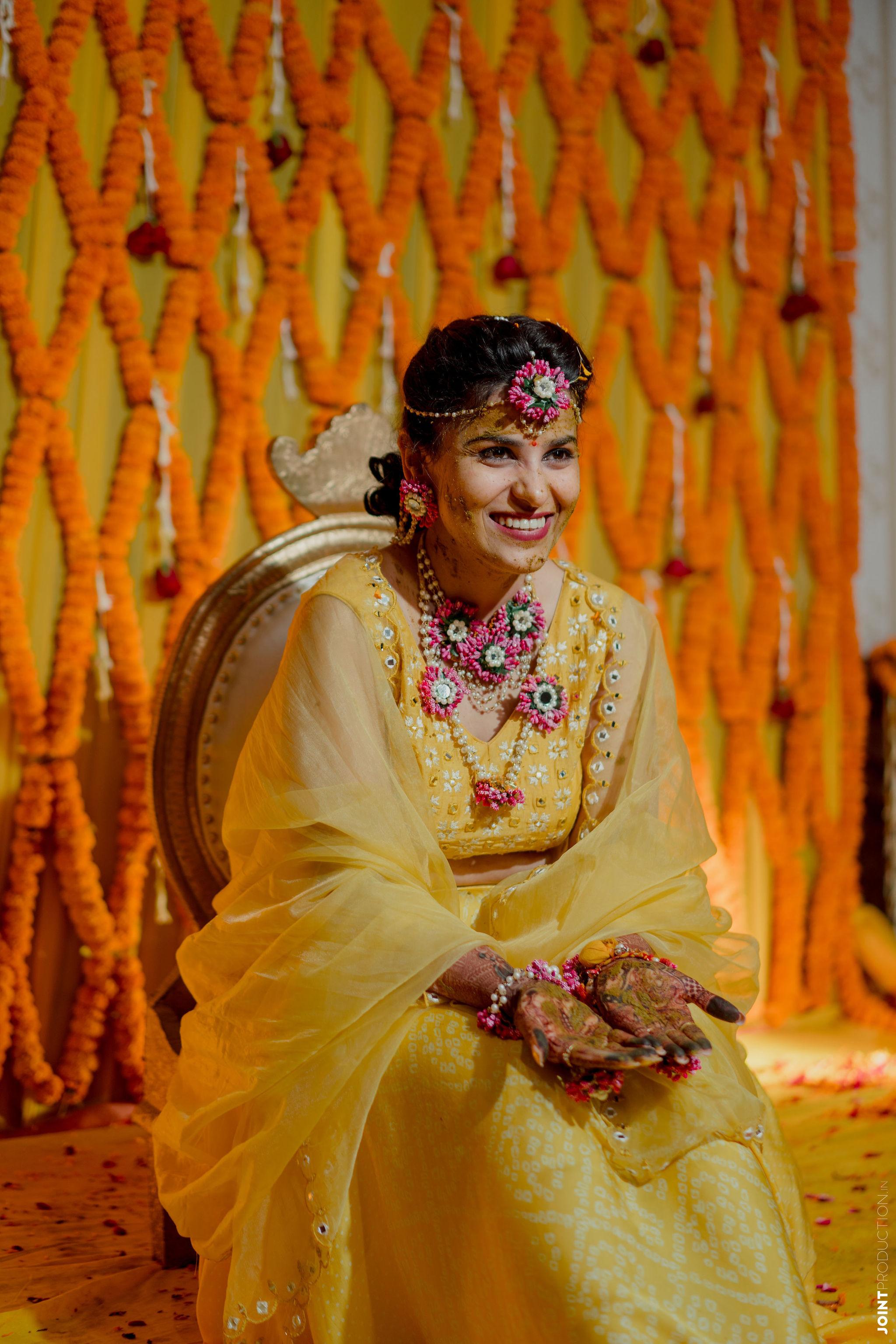 pink floral jewellery and yellow lehenga for haldi