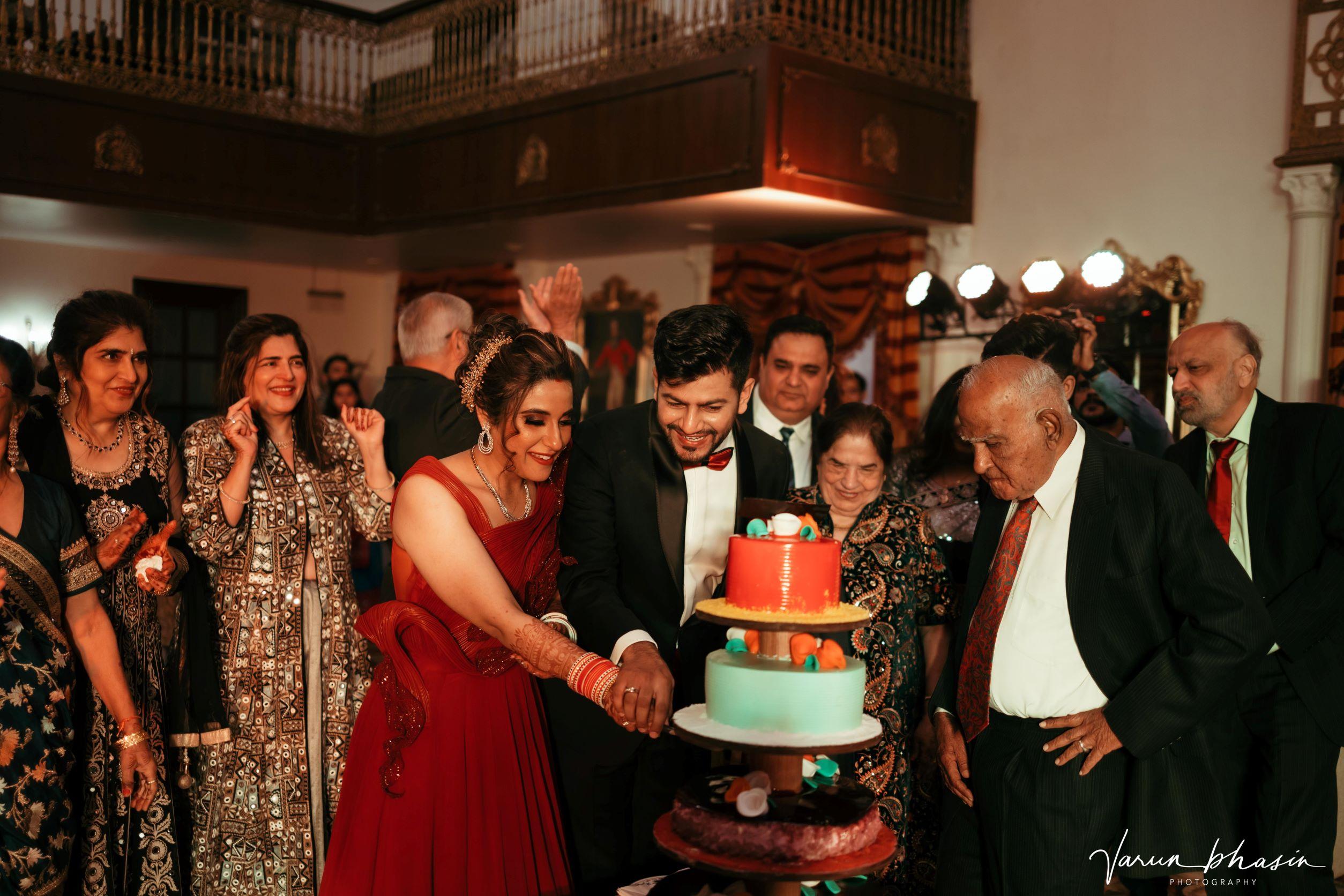 punjabi couple cutting their wedding cake