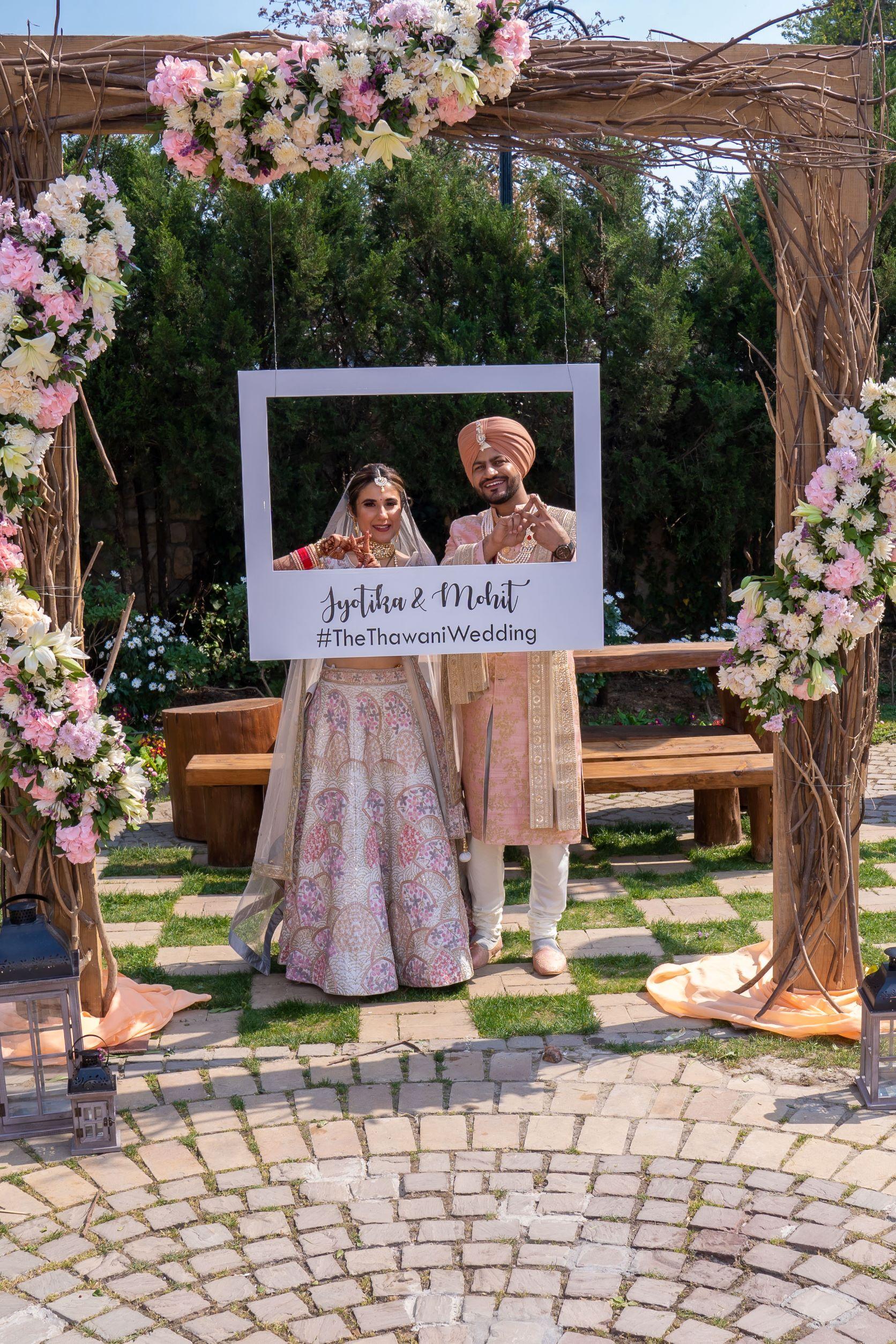punjabi couple poses with their wedding hashtag